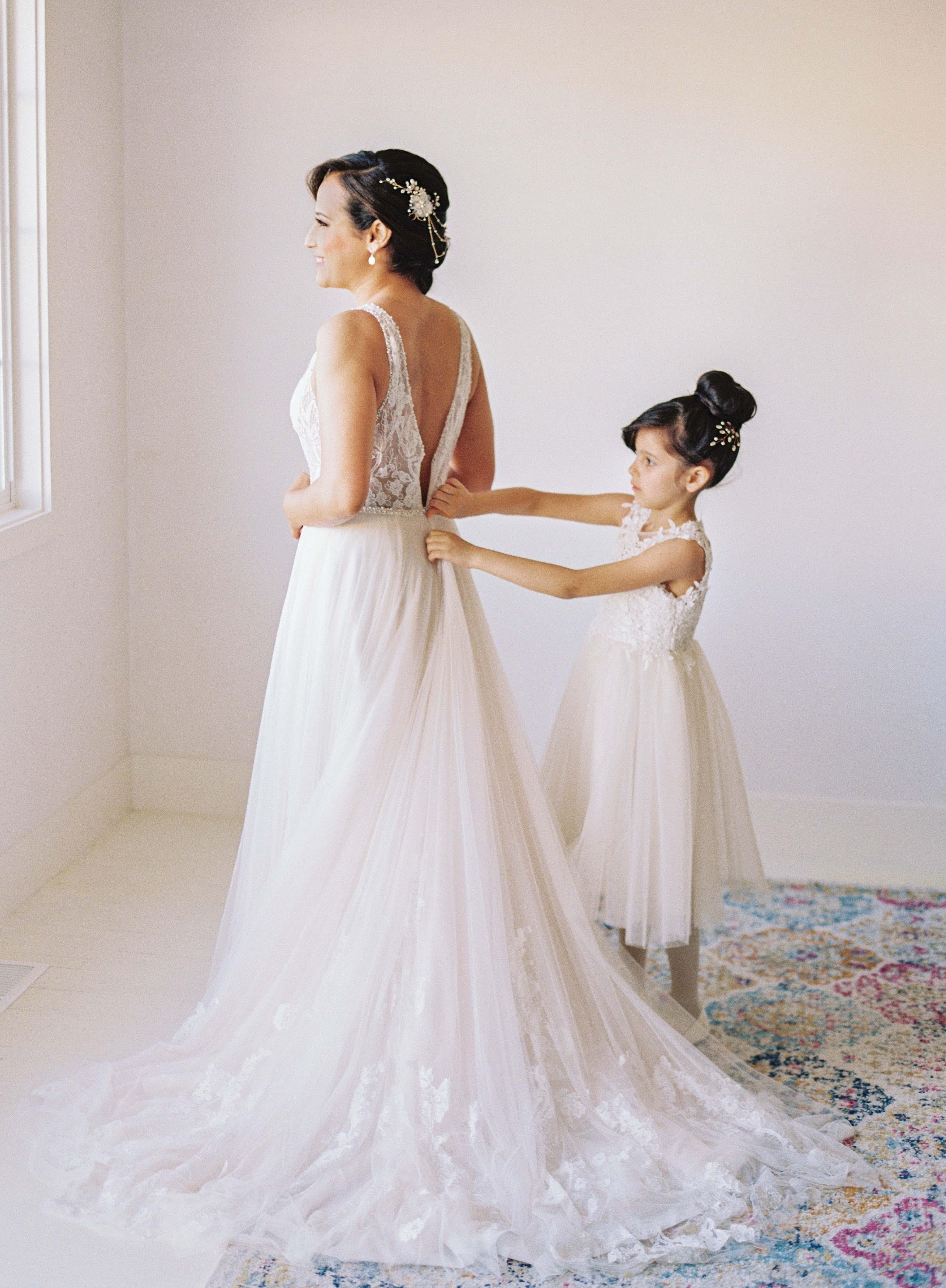 girl helps bride wearing wedding dress