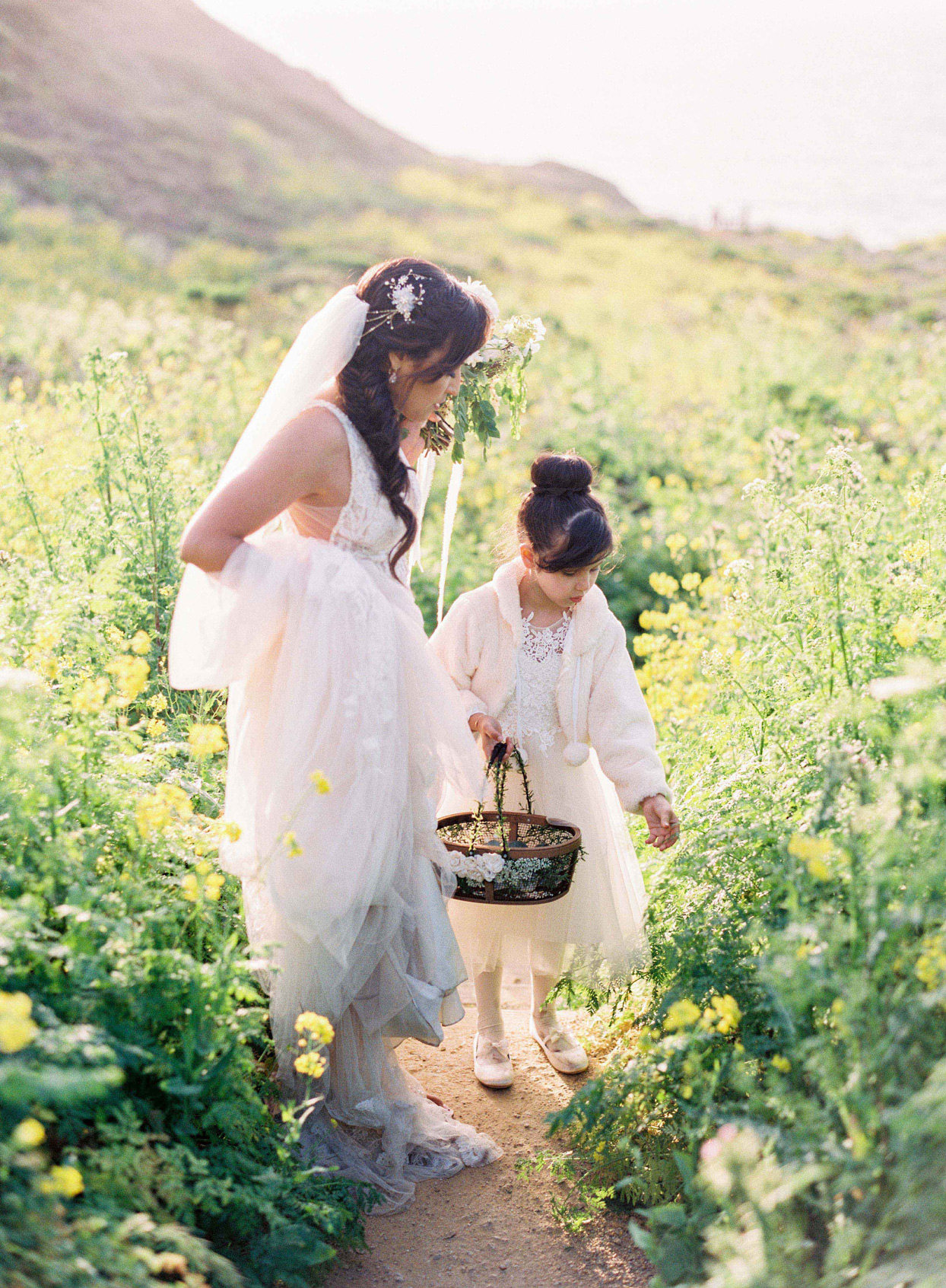 girl and bride pick flowers for wedding ceremony