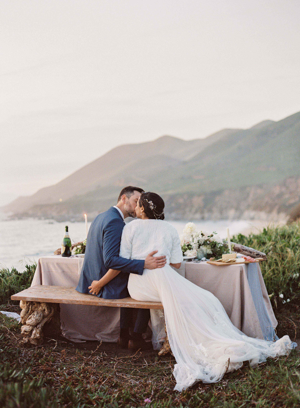 bride and groom sit at wooden table outside