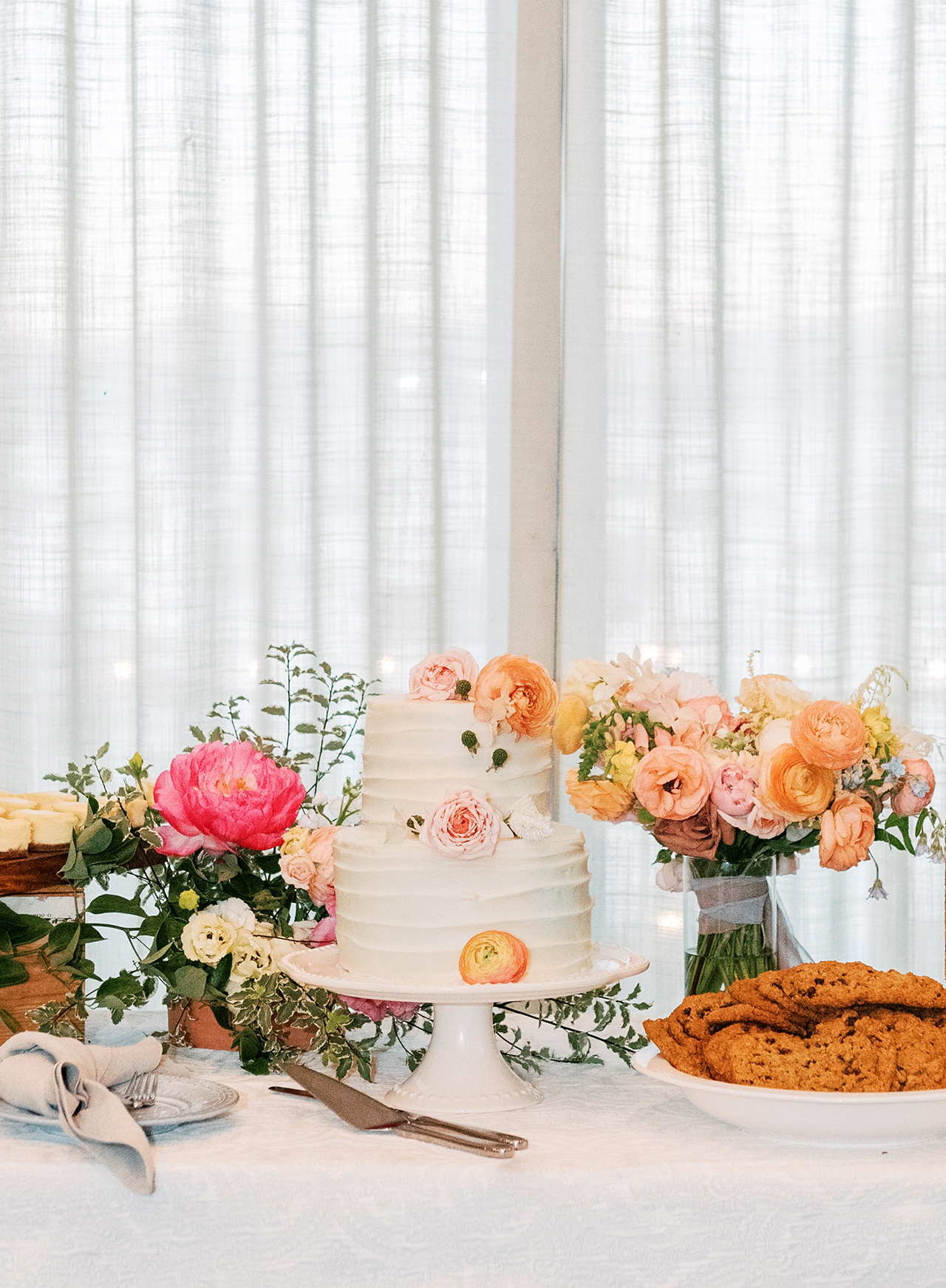 two tiered wedding cake treat table floral arrangements