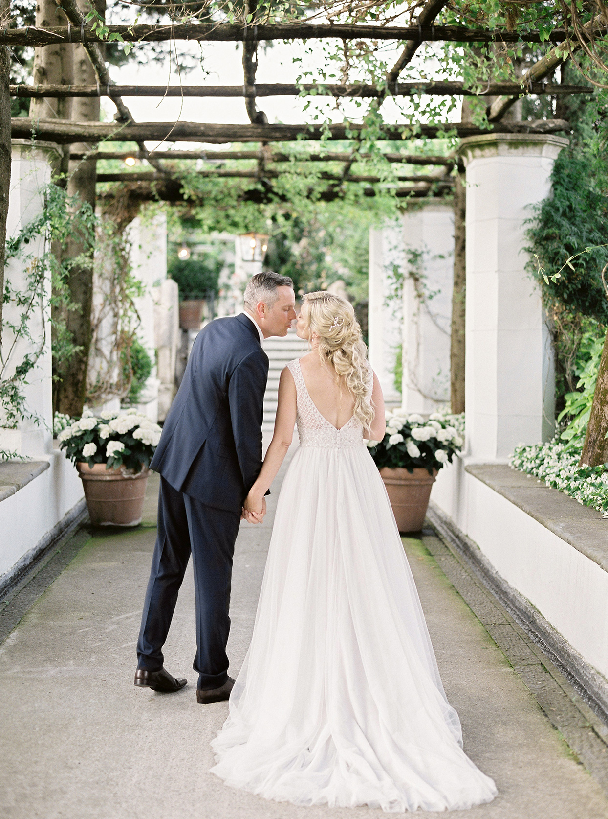 krystyna alexander wedding couple kissing under greenery
