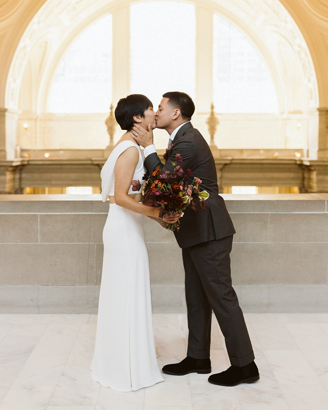 bride groom kiss dark floral bouquet window lighting