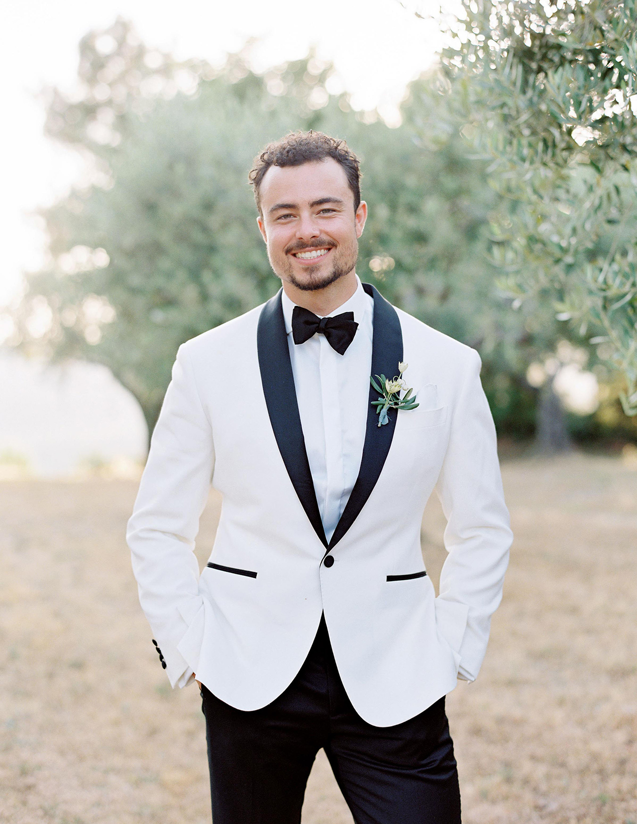 groom posing in white jacket tuxedo