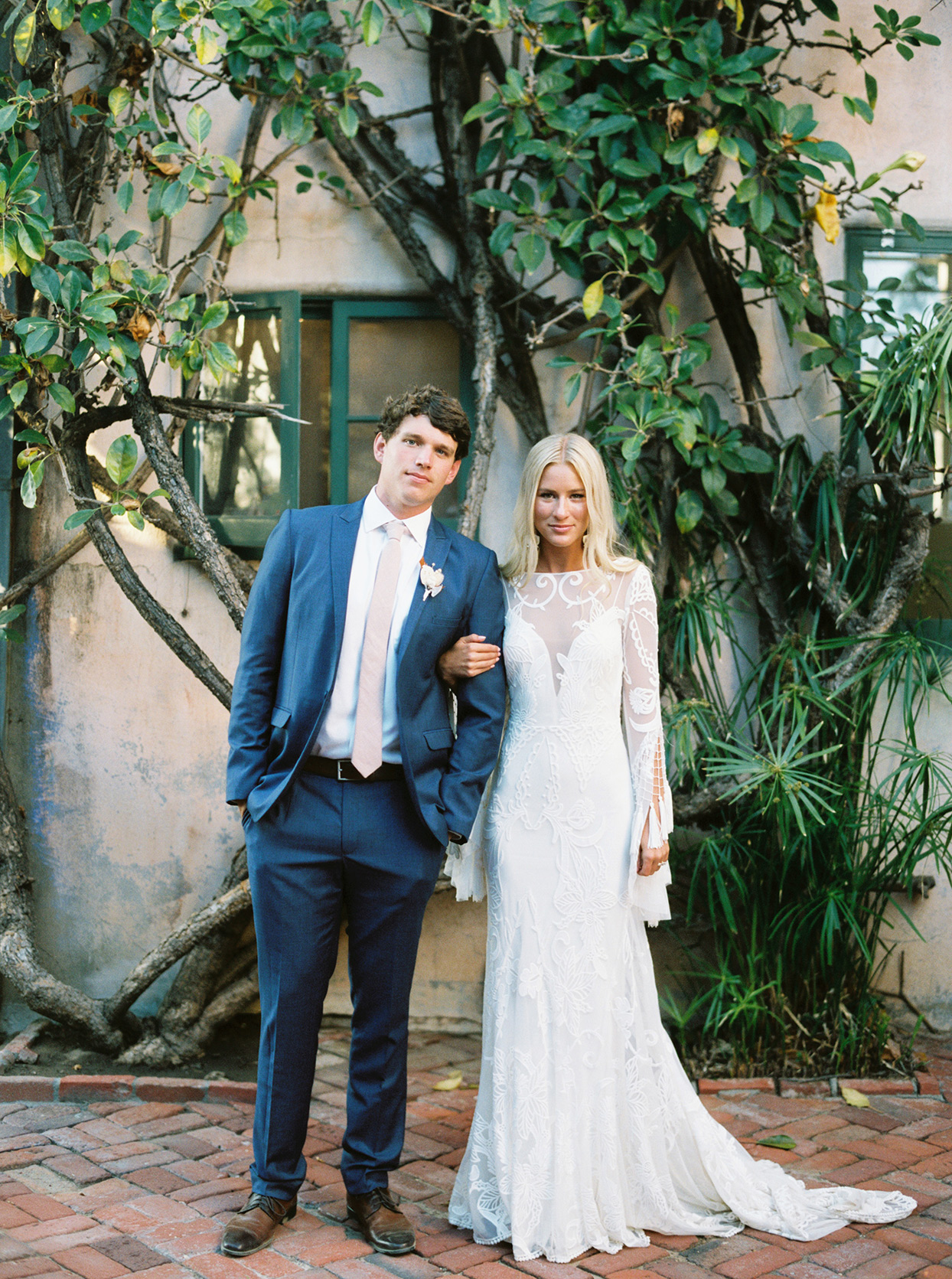 maddy will wedding couple in front of trees in courtyard