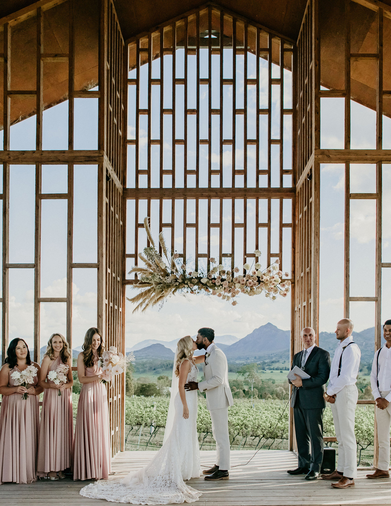bride and groom kiss during wedding surrounded by bridal party