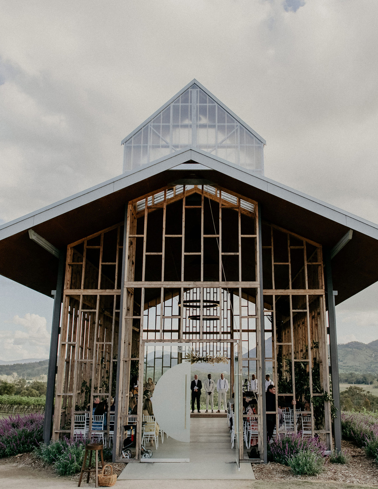 wide shot of wedding chapel building with groom and guests inside