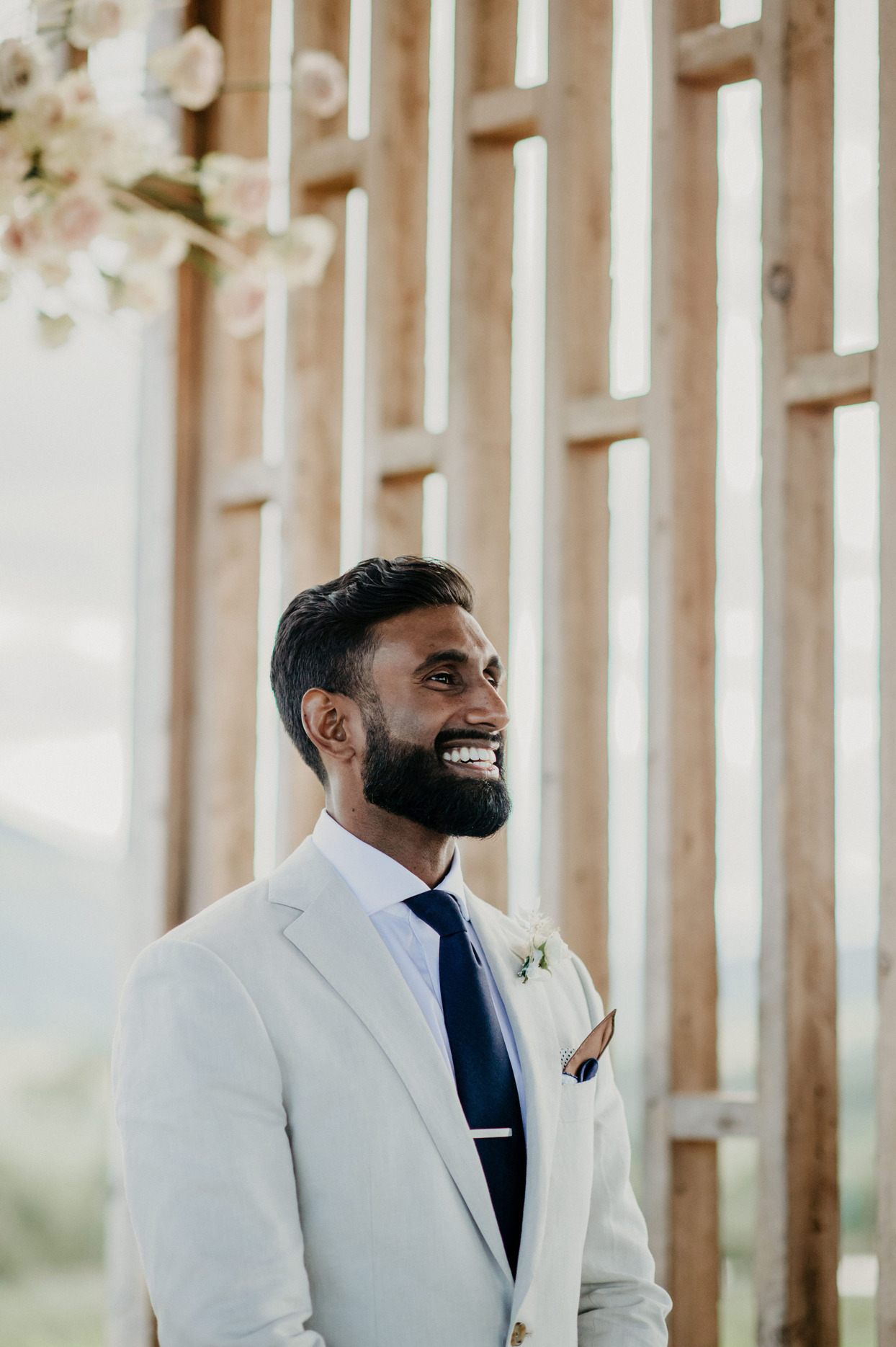 groom smiles at front of the aisle