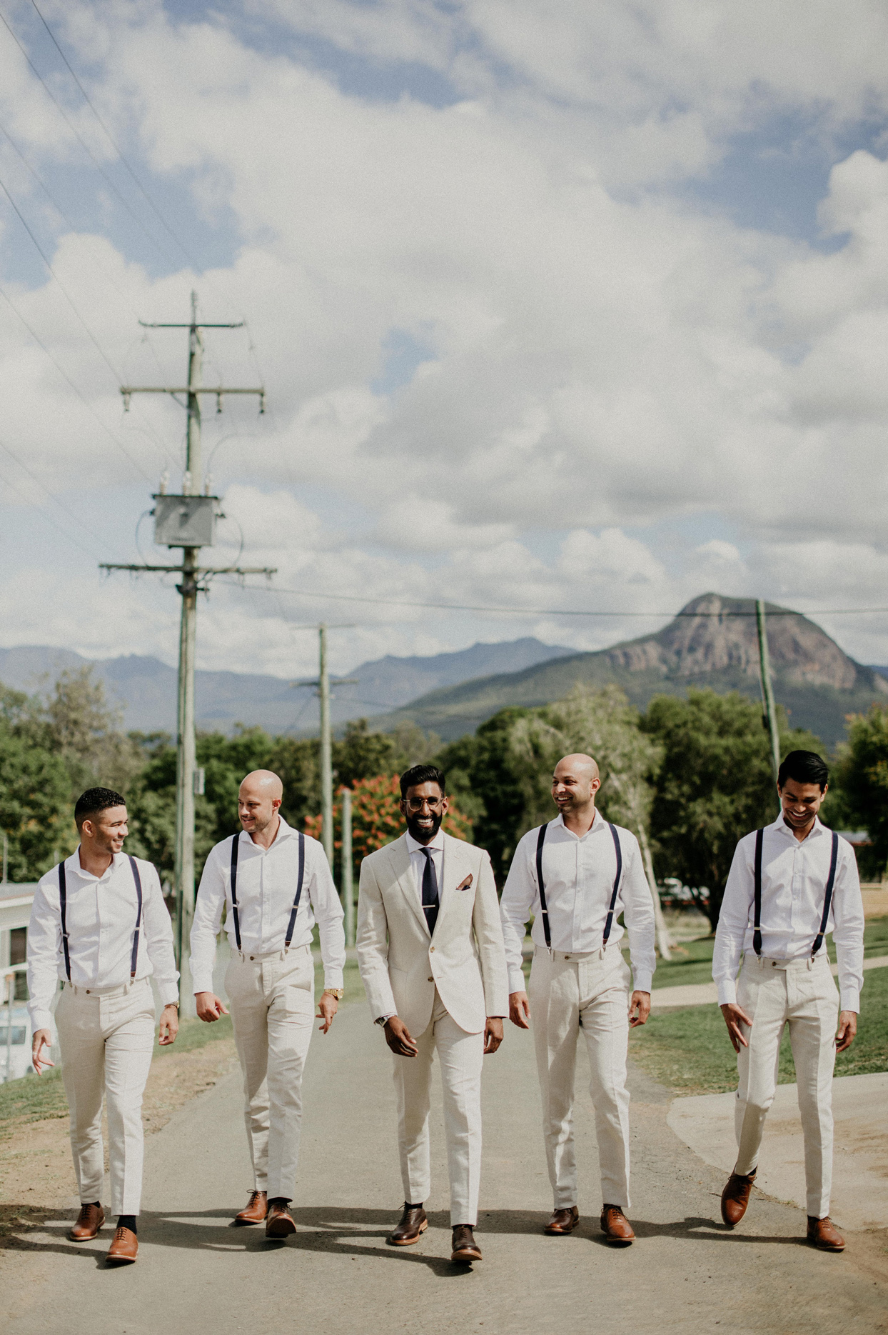 groom walking with groomsmen in white outfits