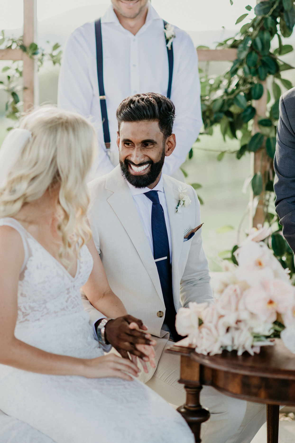 groom smiles at bride sitting at table