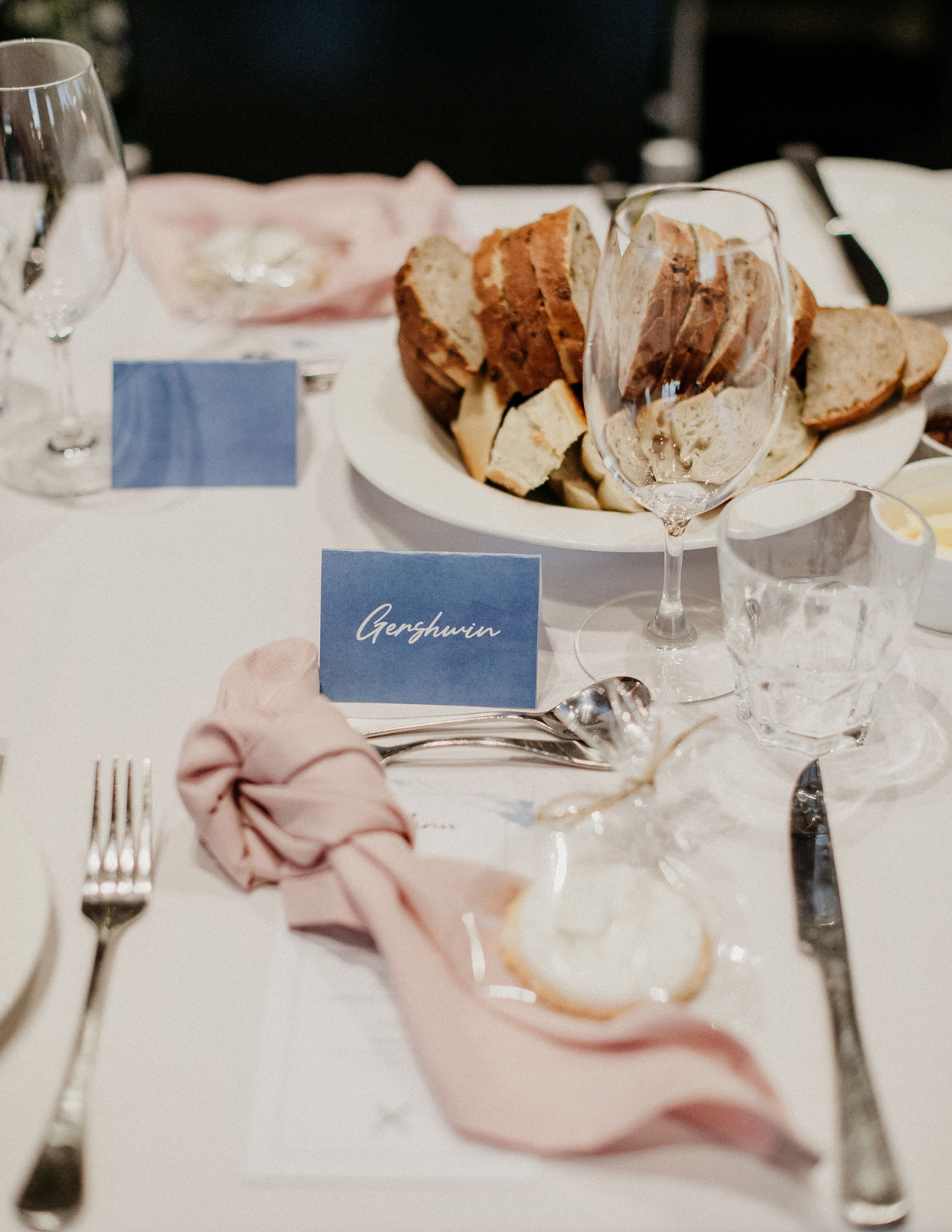 wedding place setting of pink napkin and place card with bread bowl