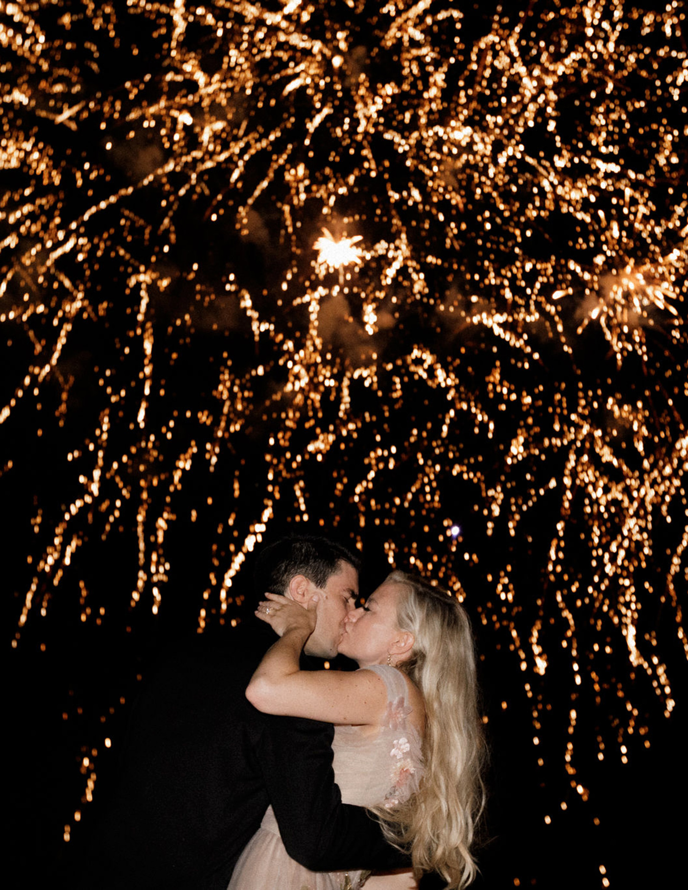 night shot wedding couple kissing under fireworks