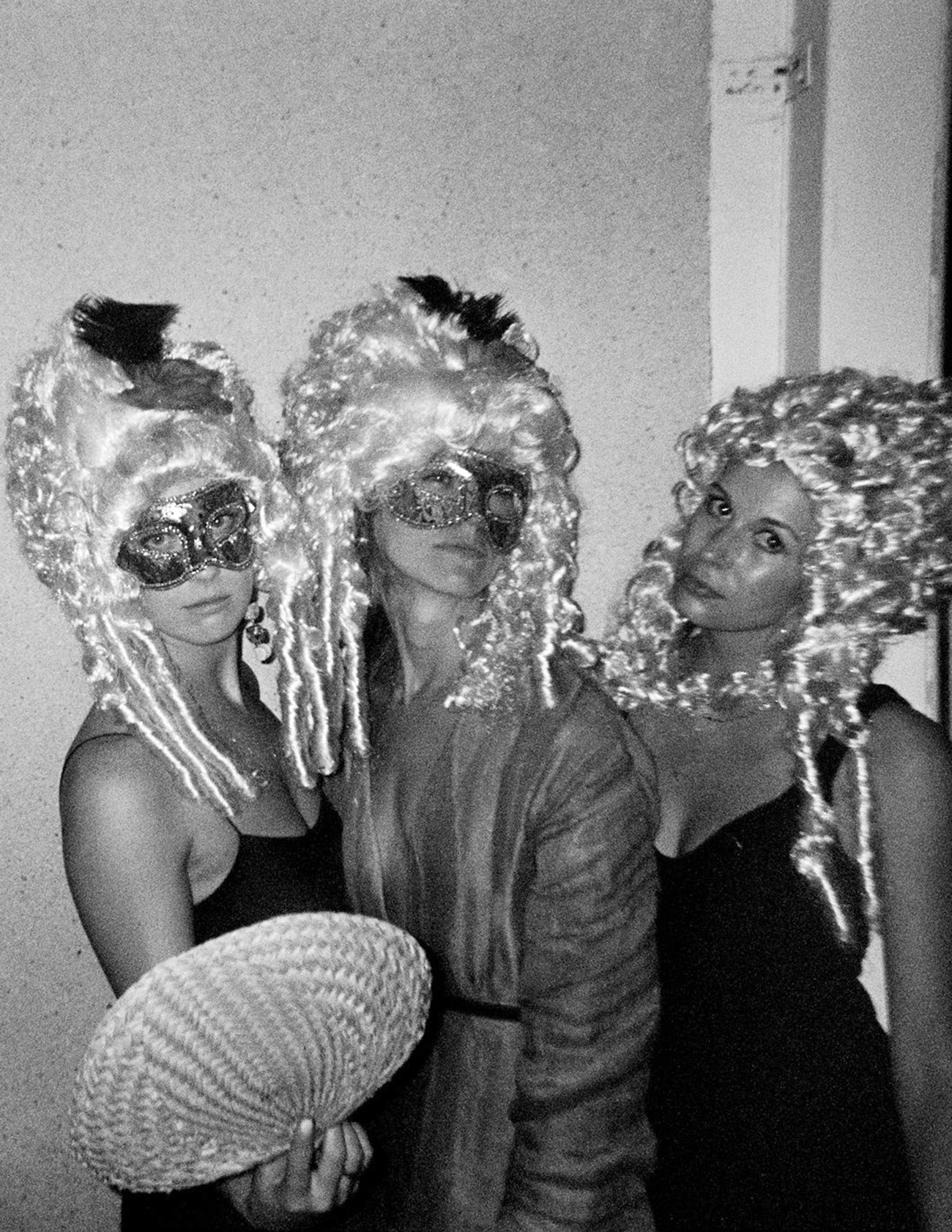 black and white portrait three women wearing masks and wigs