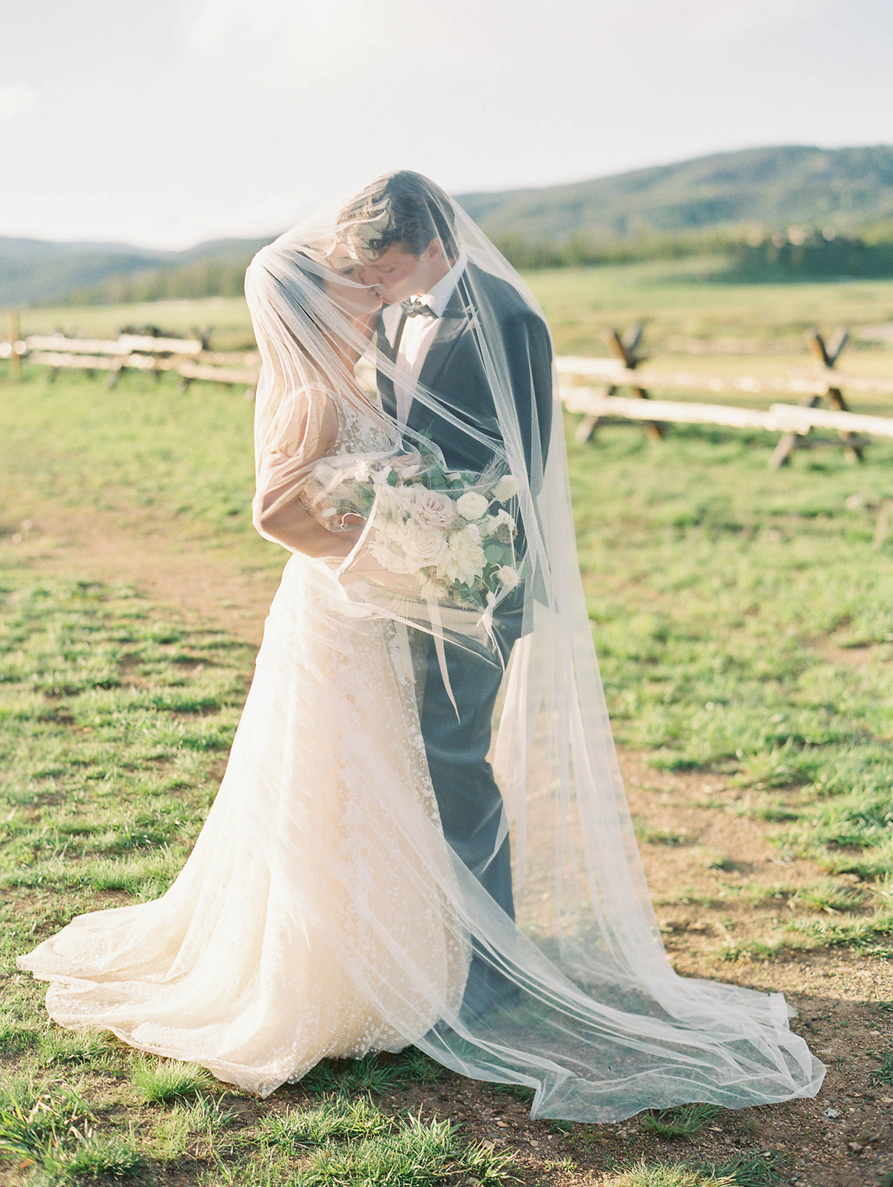 bride groom kiss under long veil