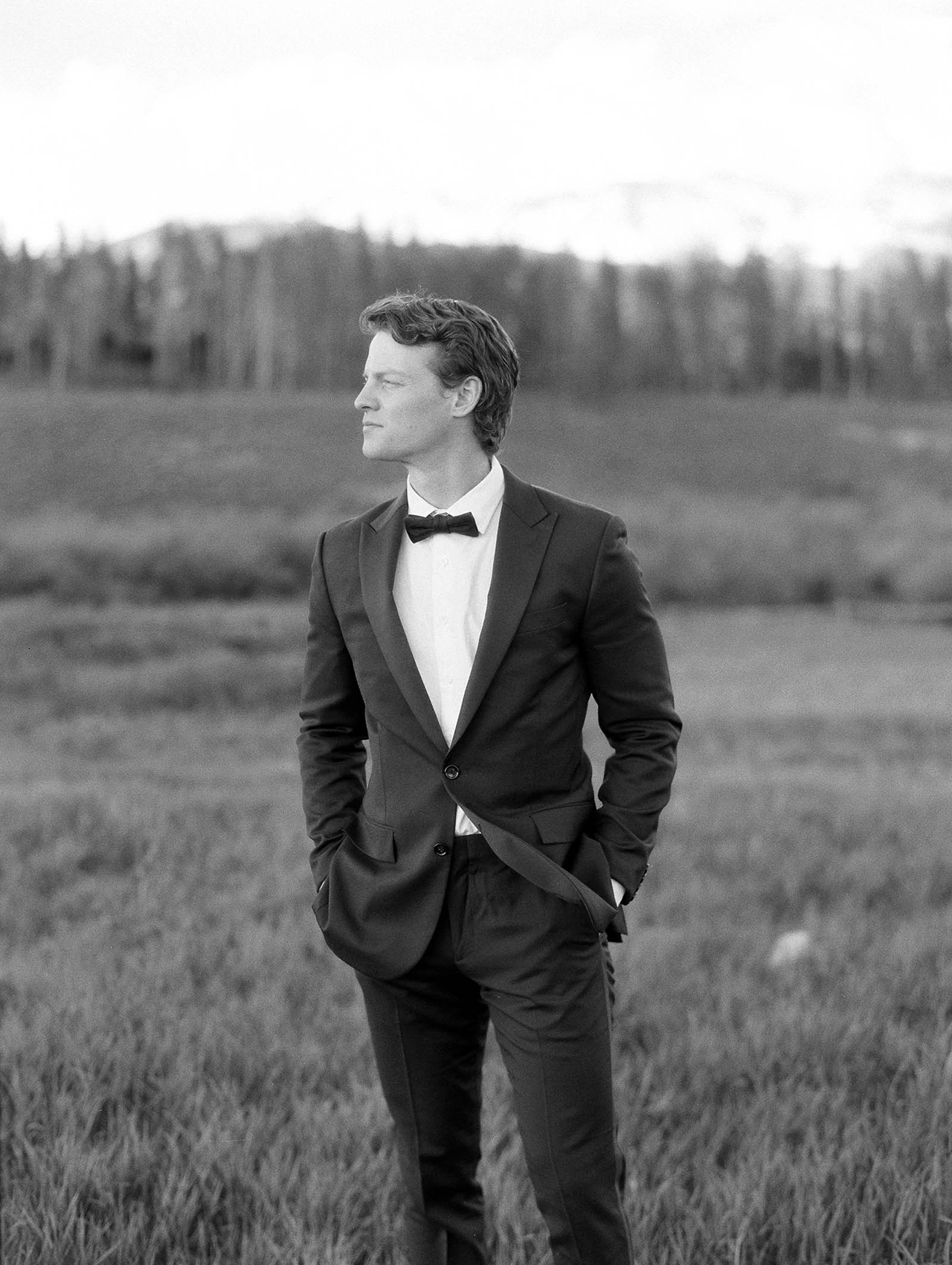 groom pose black tuxedo bowtie outdoors