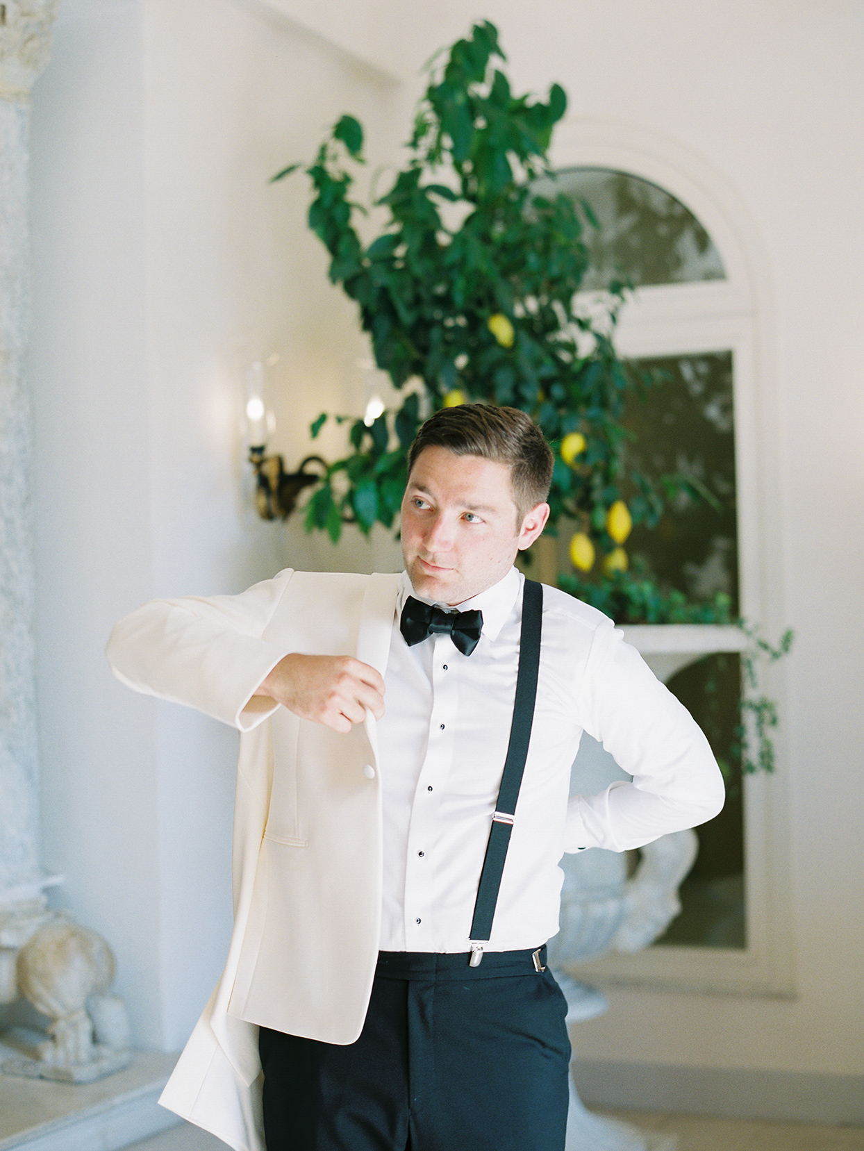 jacqueline david wedding groom putting on coat