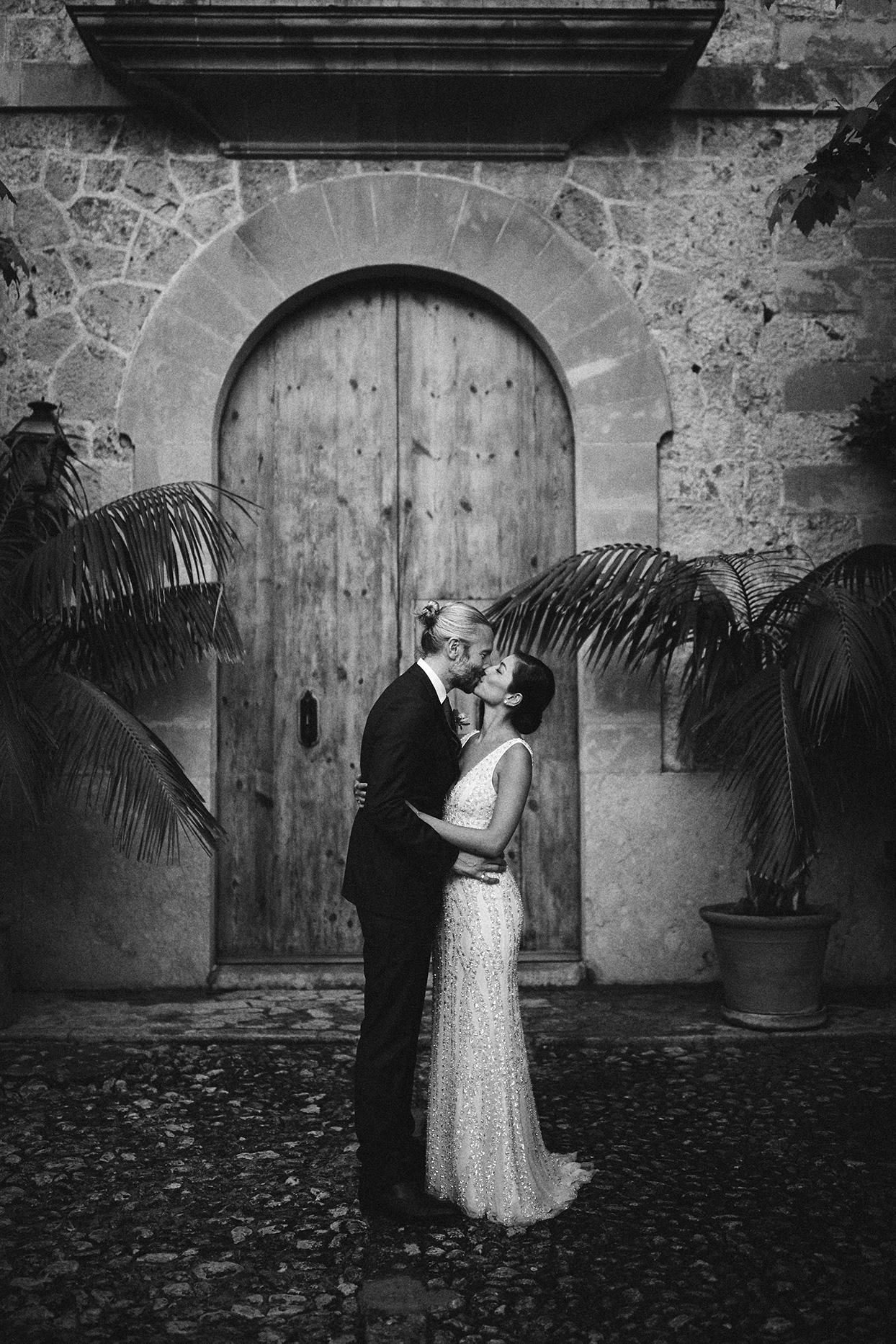 pomme daniel wedding couple kiss in front of rustic door