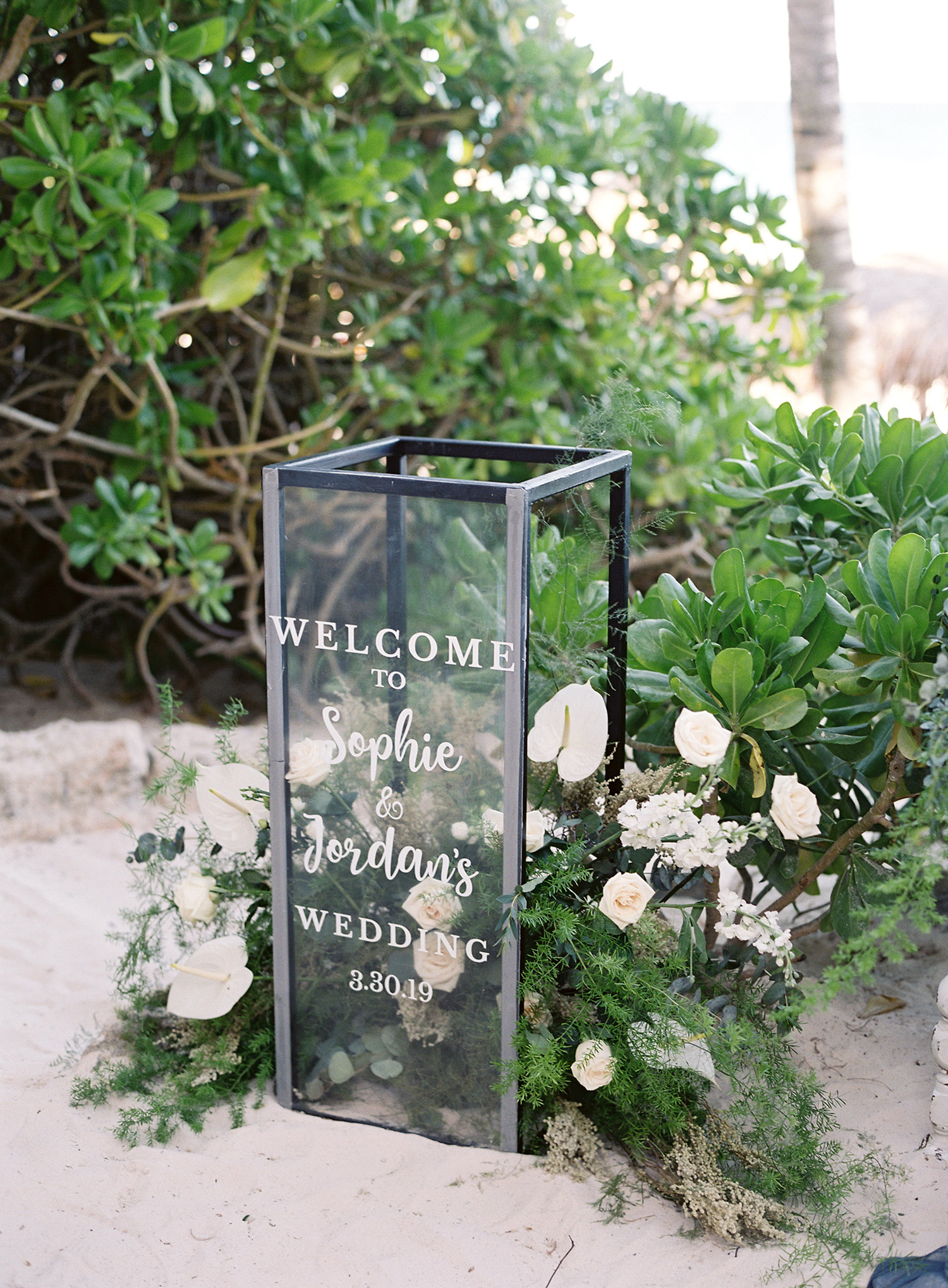 glass welcome sign with greenery white flowers