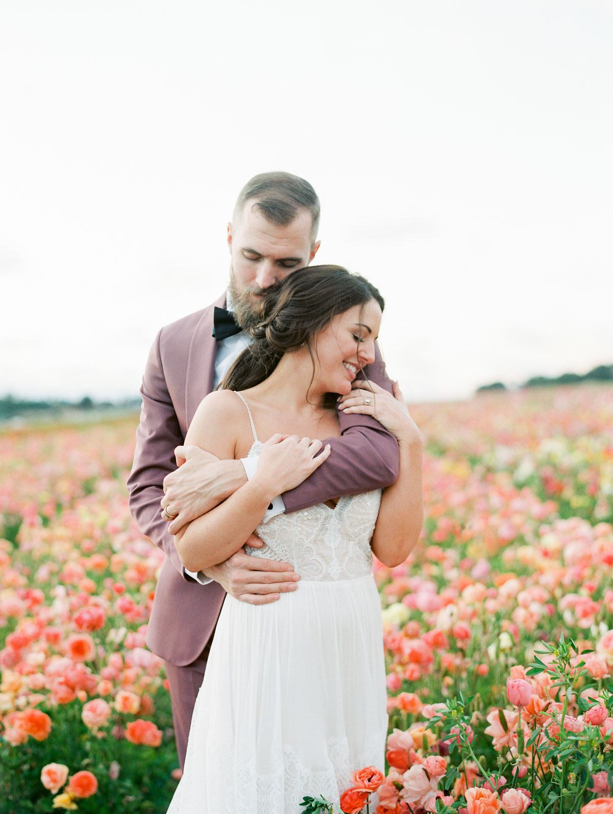 groom embracing bride from behind bride smiling surrounded by pink flowers