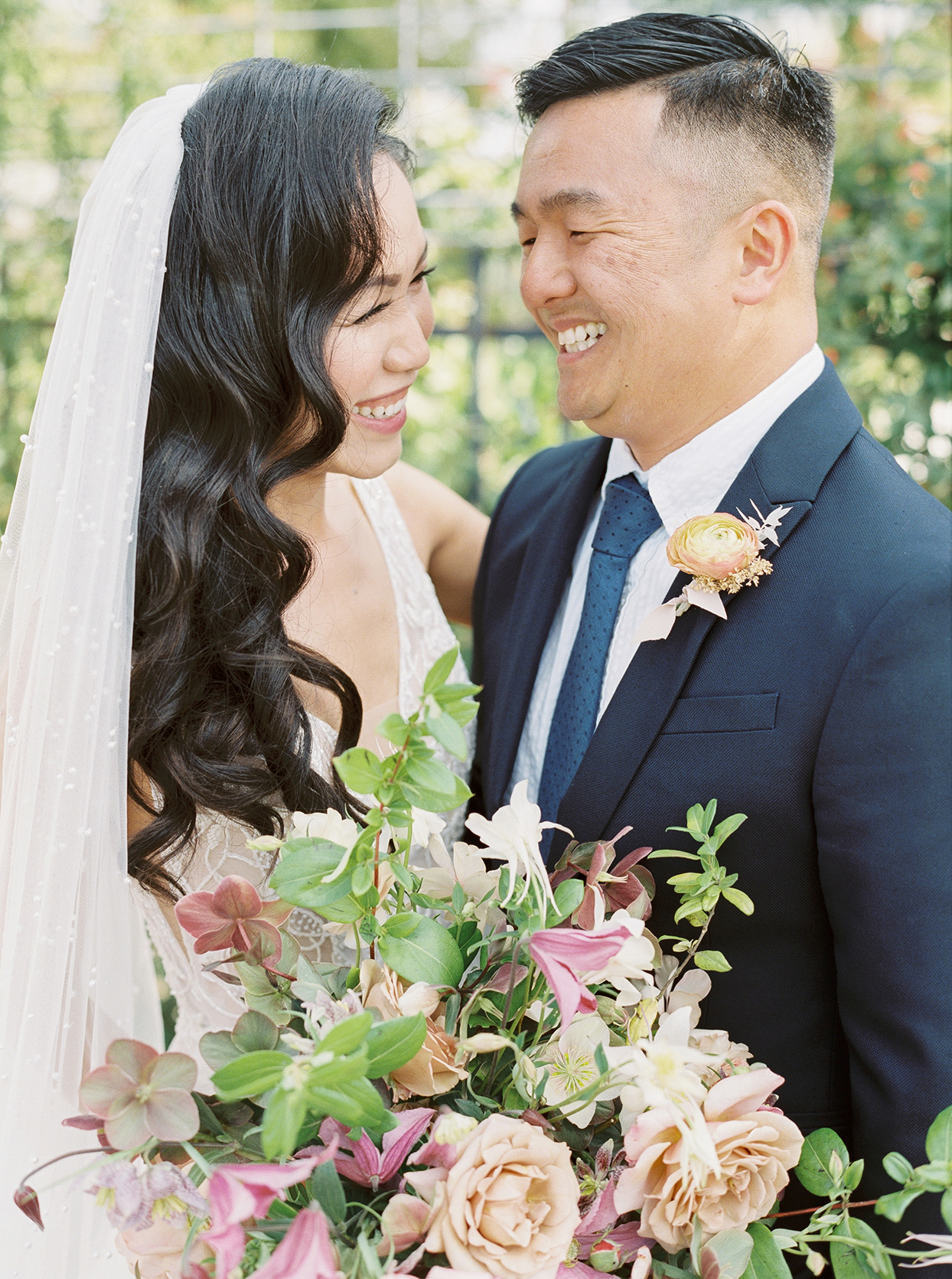 thuy kahn wedding couple smiling with flowers