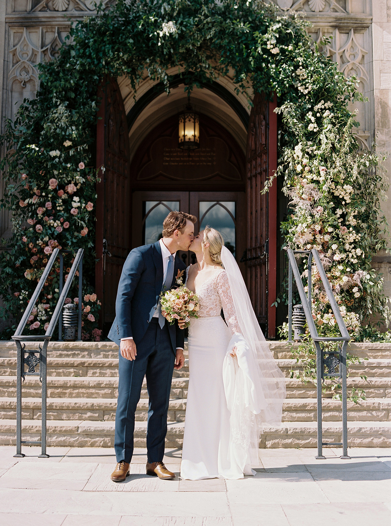 bride groom kiss in front of floral arch church entrance