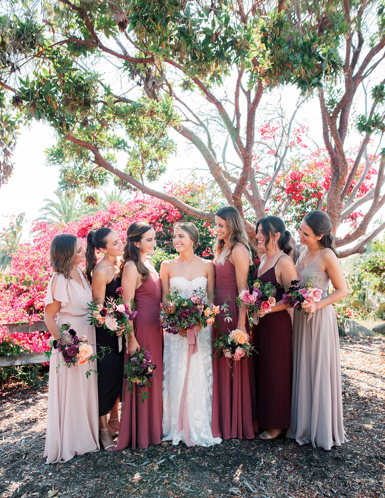 bride bridesmaids pink shade dresses pose outdoors