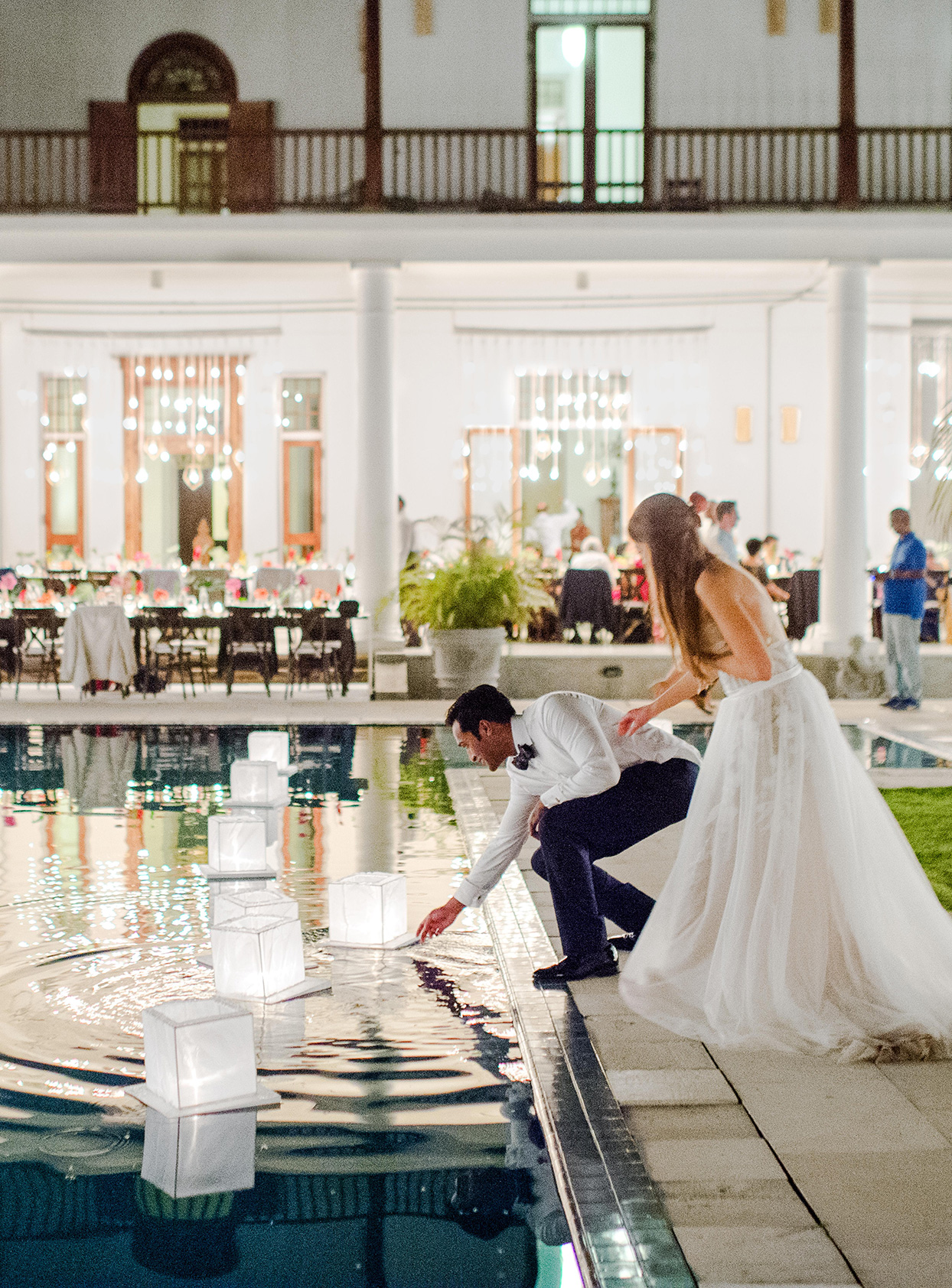kelly sanjiv wedding couple putting lanterns in pool