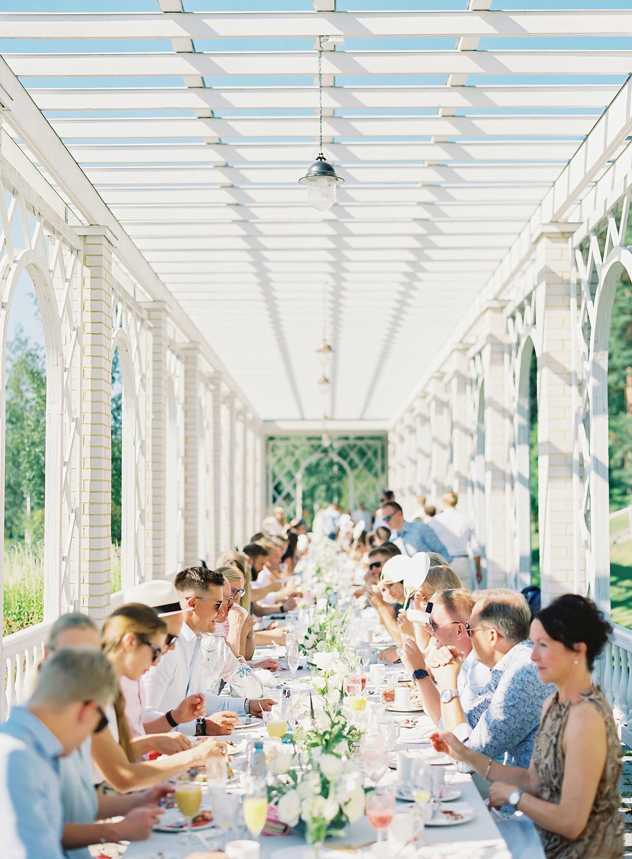 laura alexander wedding brunch guests at long outdoor table