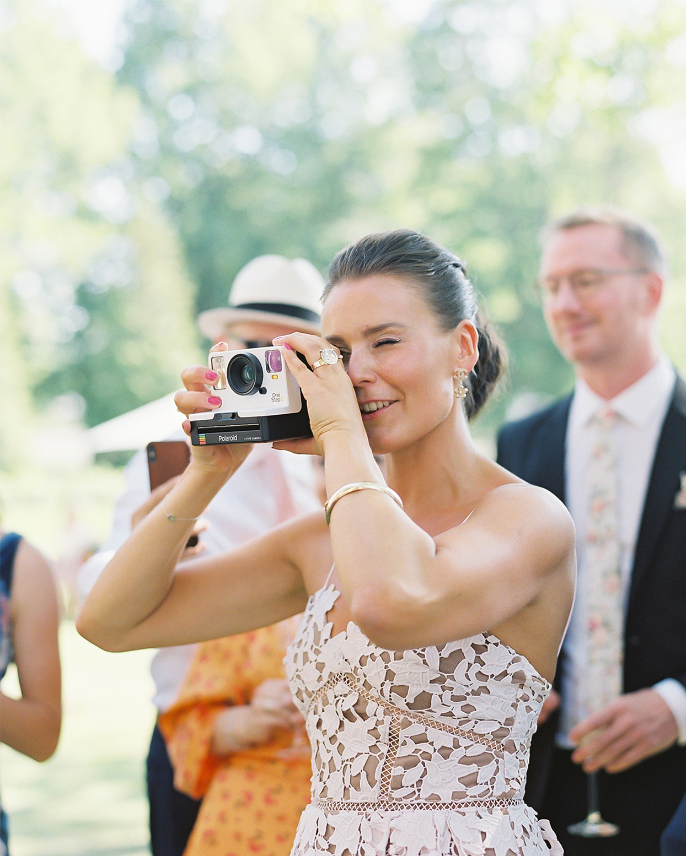 laura alexander wedding cocktail hour girl taking photo with polaroid