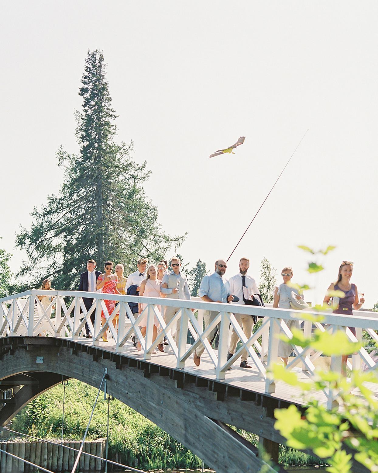laura alexander wedding guests crossing bridge