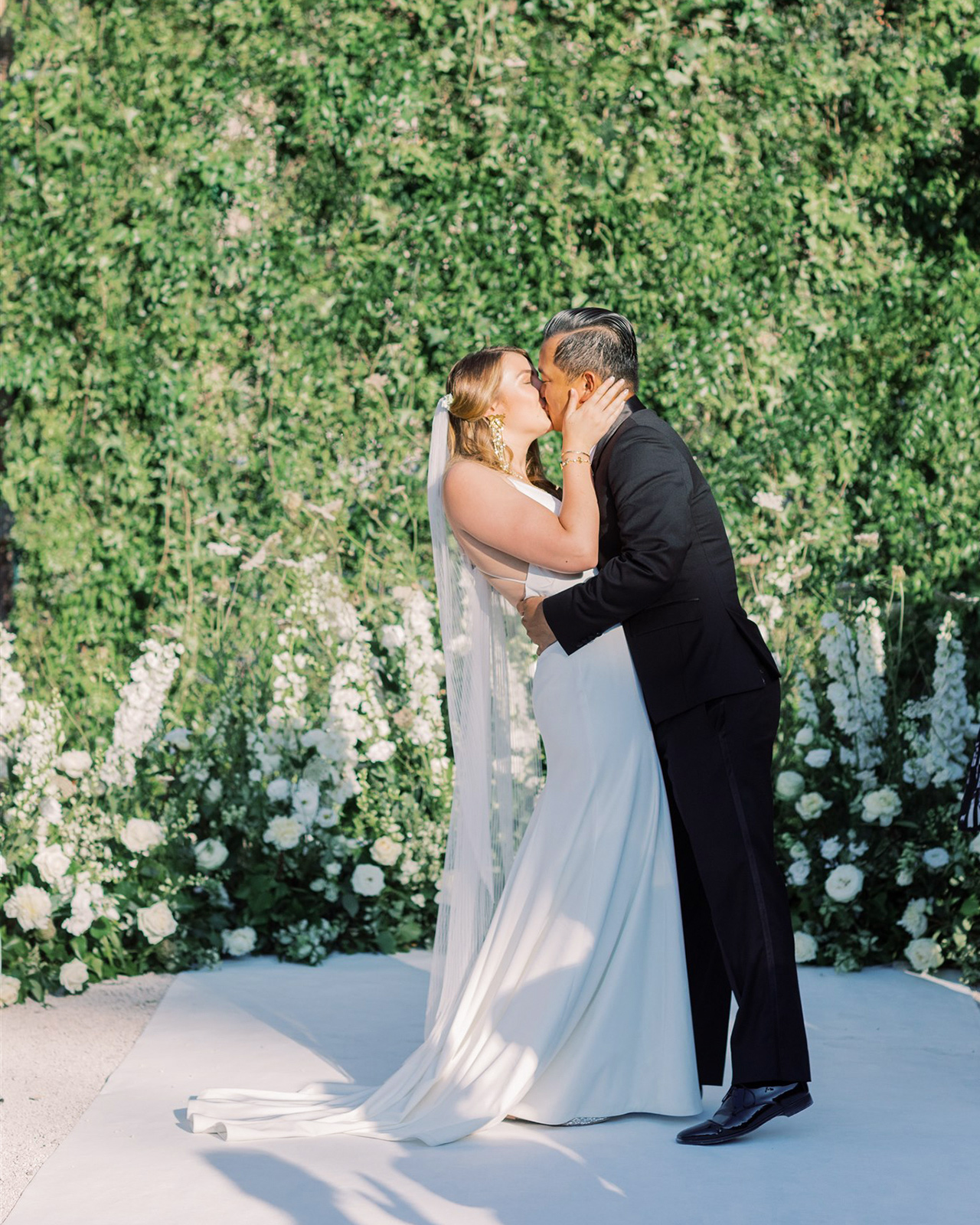 bride groom kiss outdoor wedding space white flower backdrop