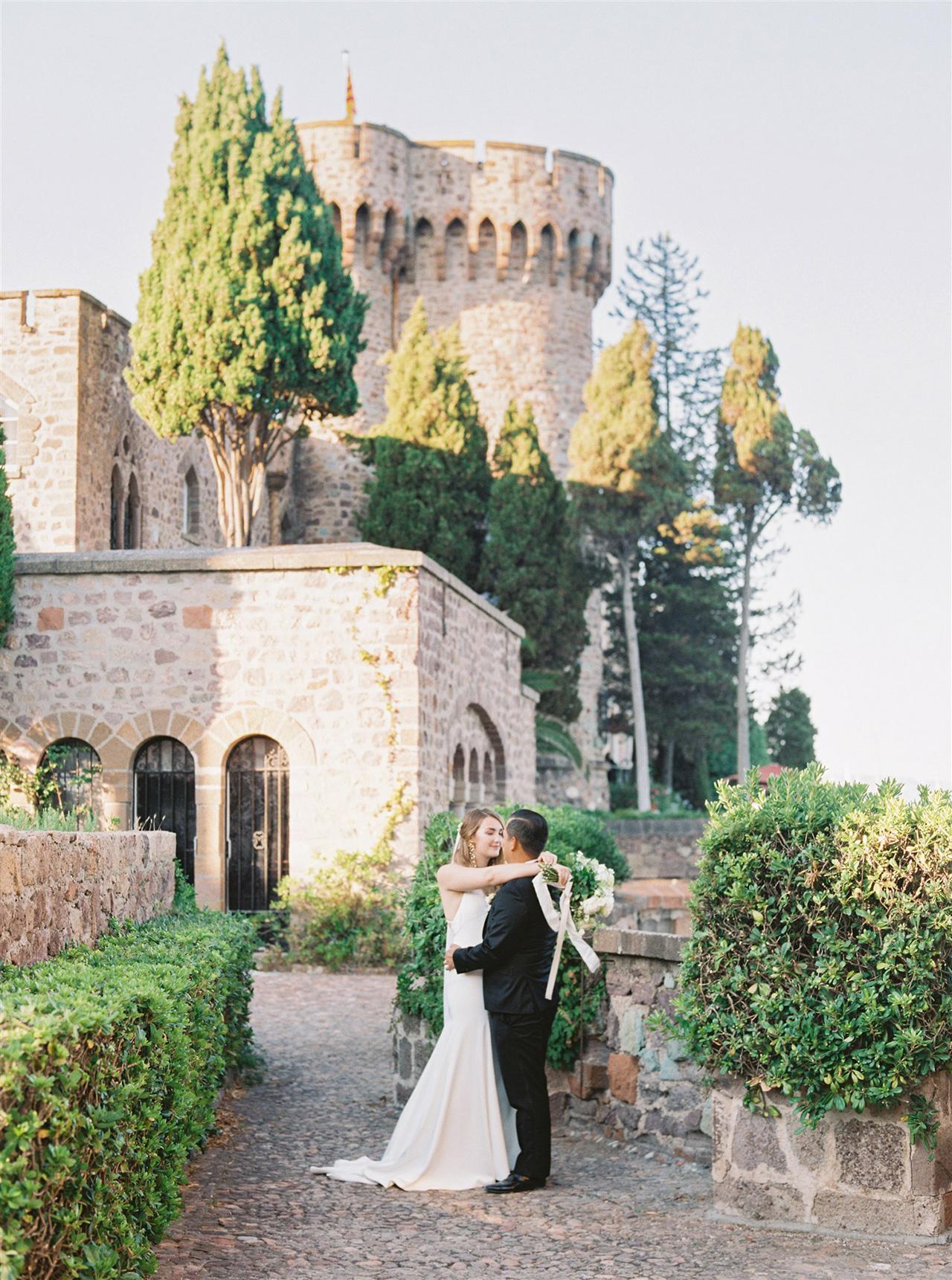 wedding couple pose outside historic castle