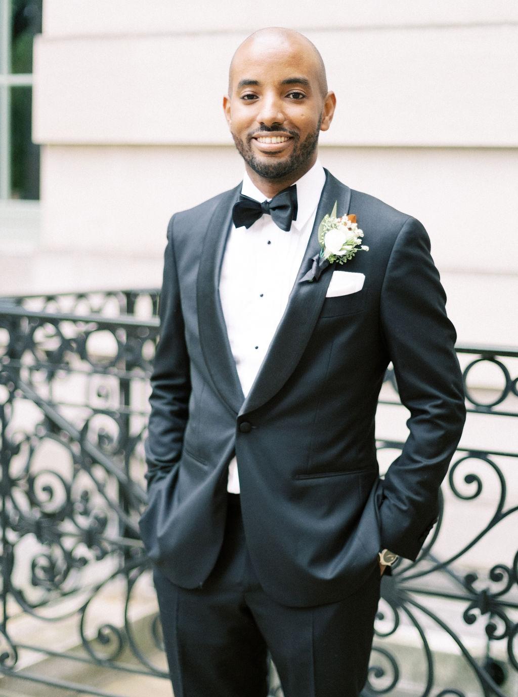 megan henock wedding groom portrait in front of fence