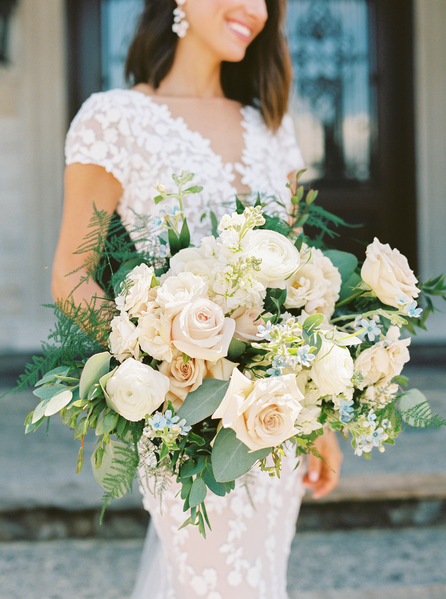roses, ranunculus, blue tweedia, and greenery bridal wedding bouquet
