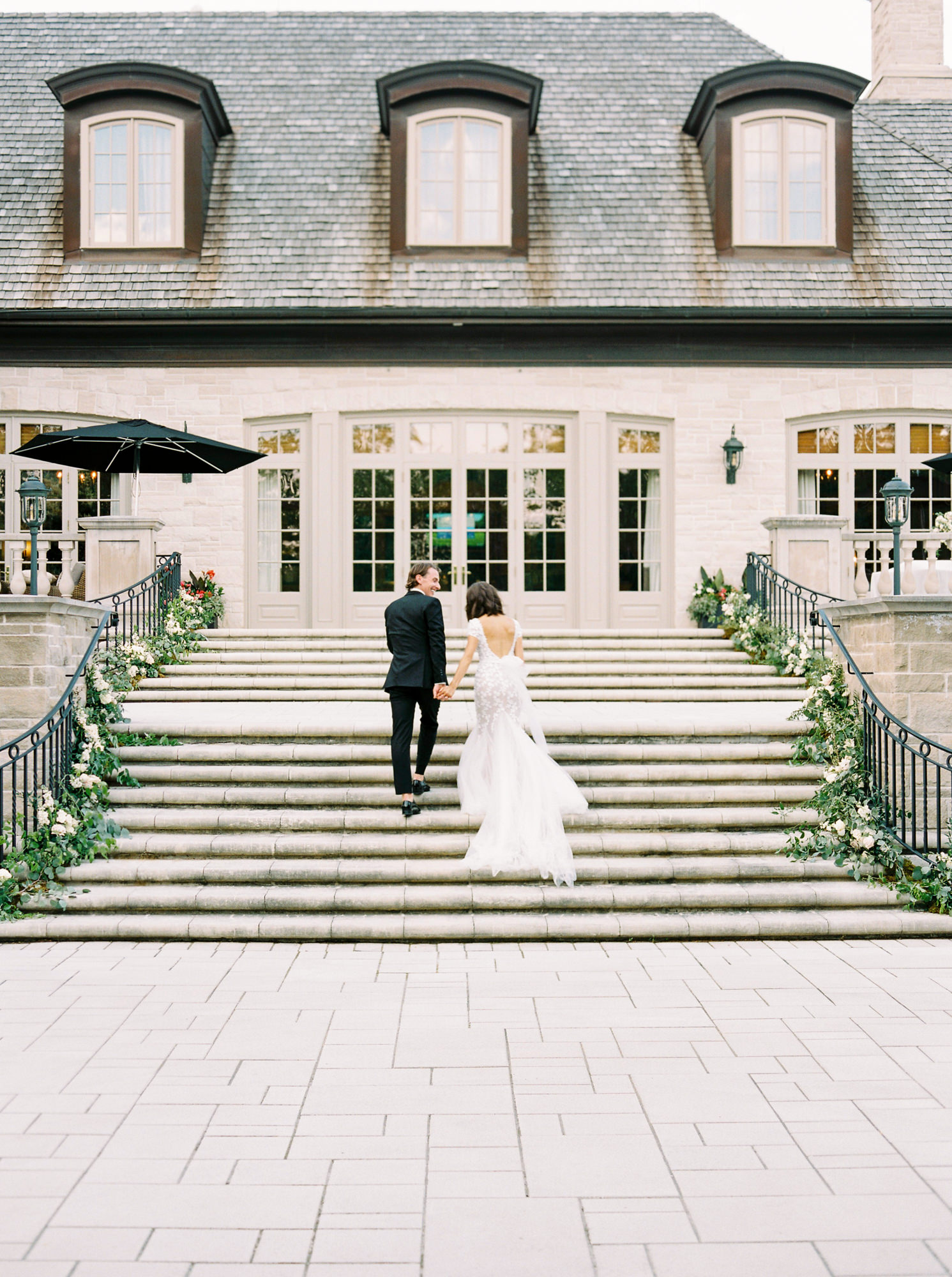 bride and groom walking up outdoor stairs
