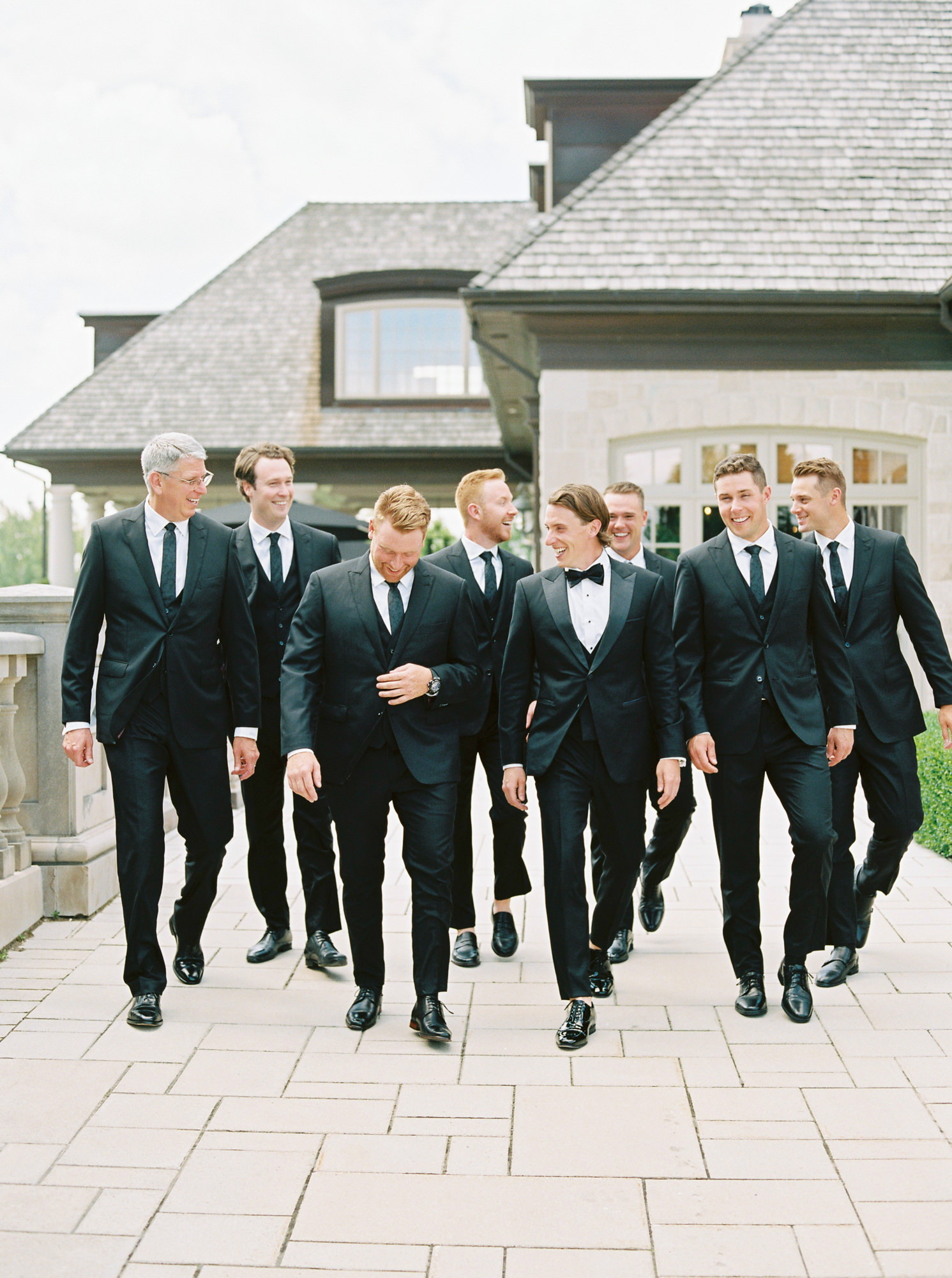 groom with groomsmen smiling all wearing black suits