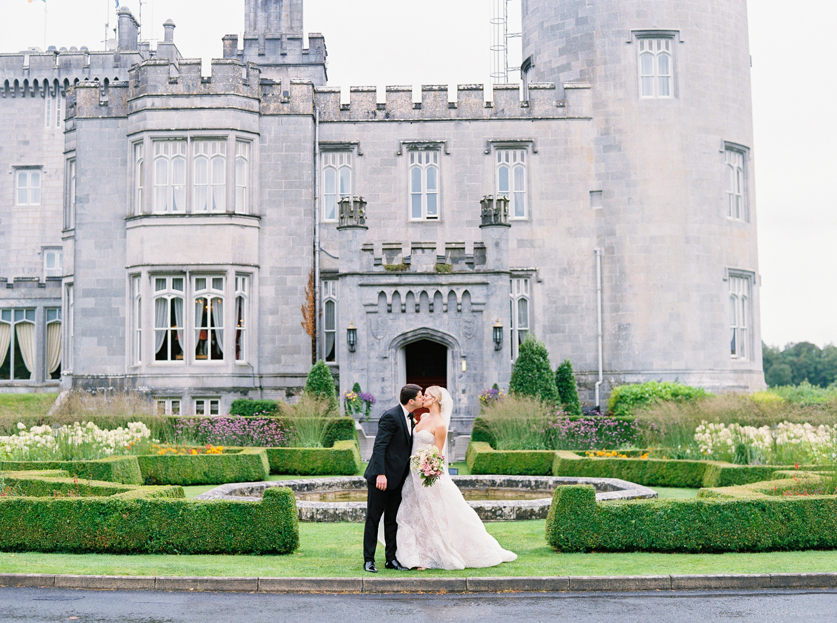 bride and groom kissing in front of Dromoland Castle