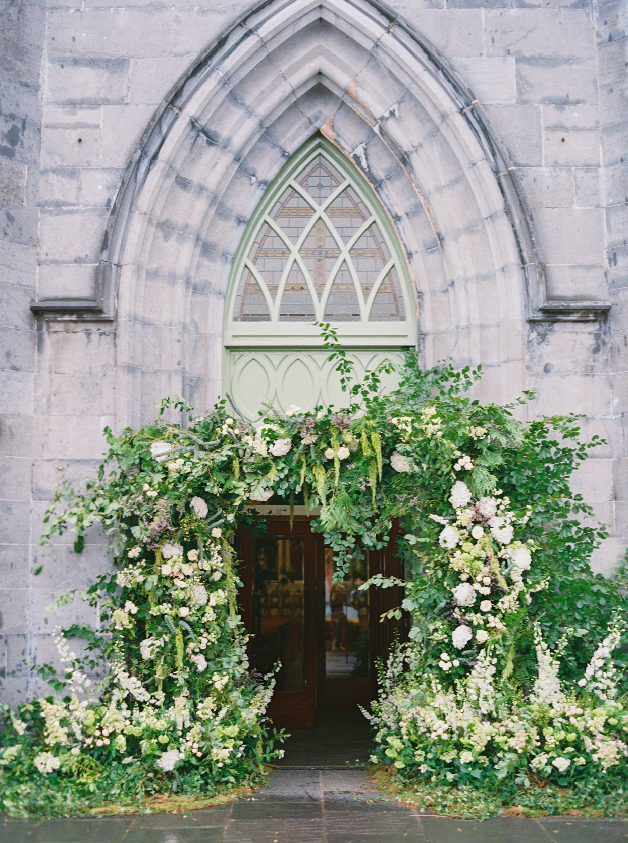 Ennis Cathedral front entry covered in greenery and floral arch