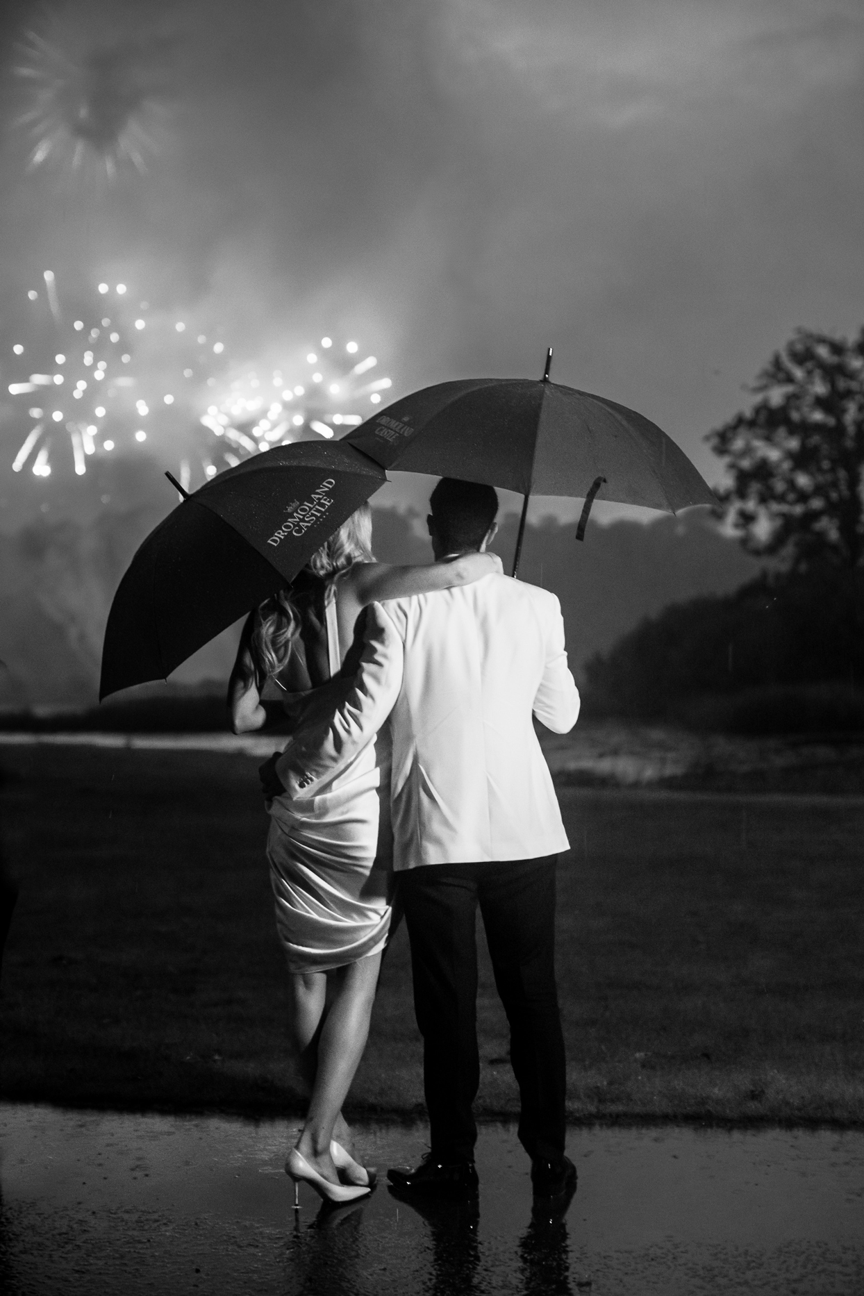 bride and groom holding umbrellas watching fireworks