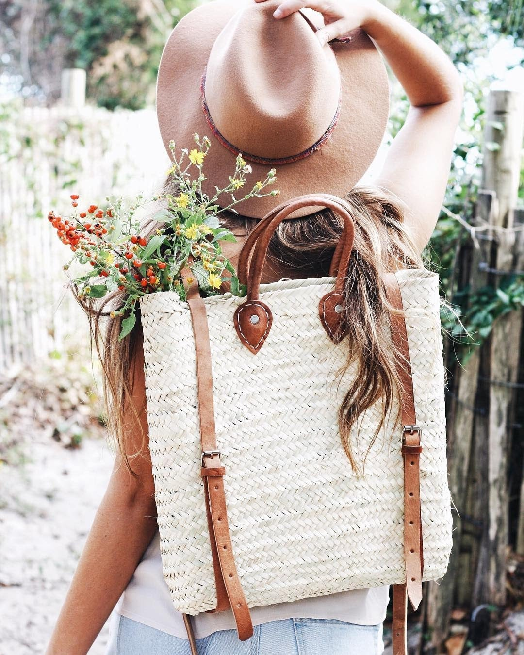 person walking carrying straw backpack with leather straps full of wildflowers