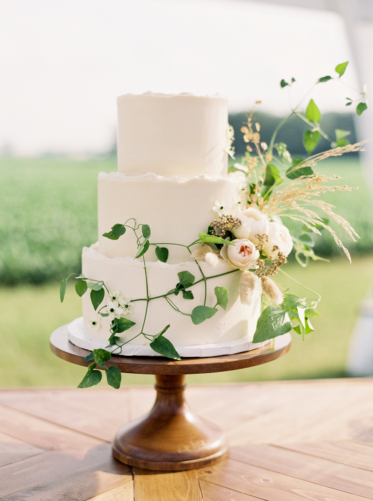 three tier wedding cake displayed on wood table