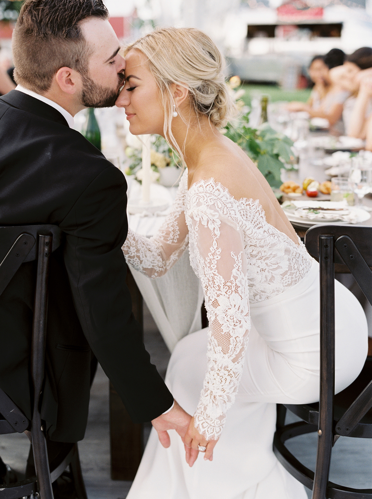 groom kiss bride forehead outdoor reception