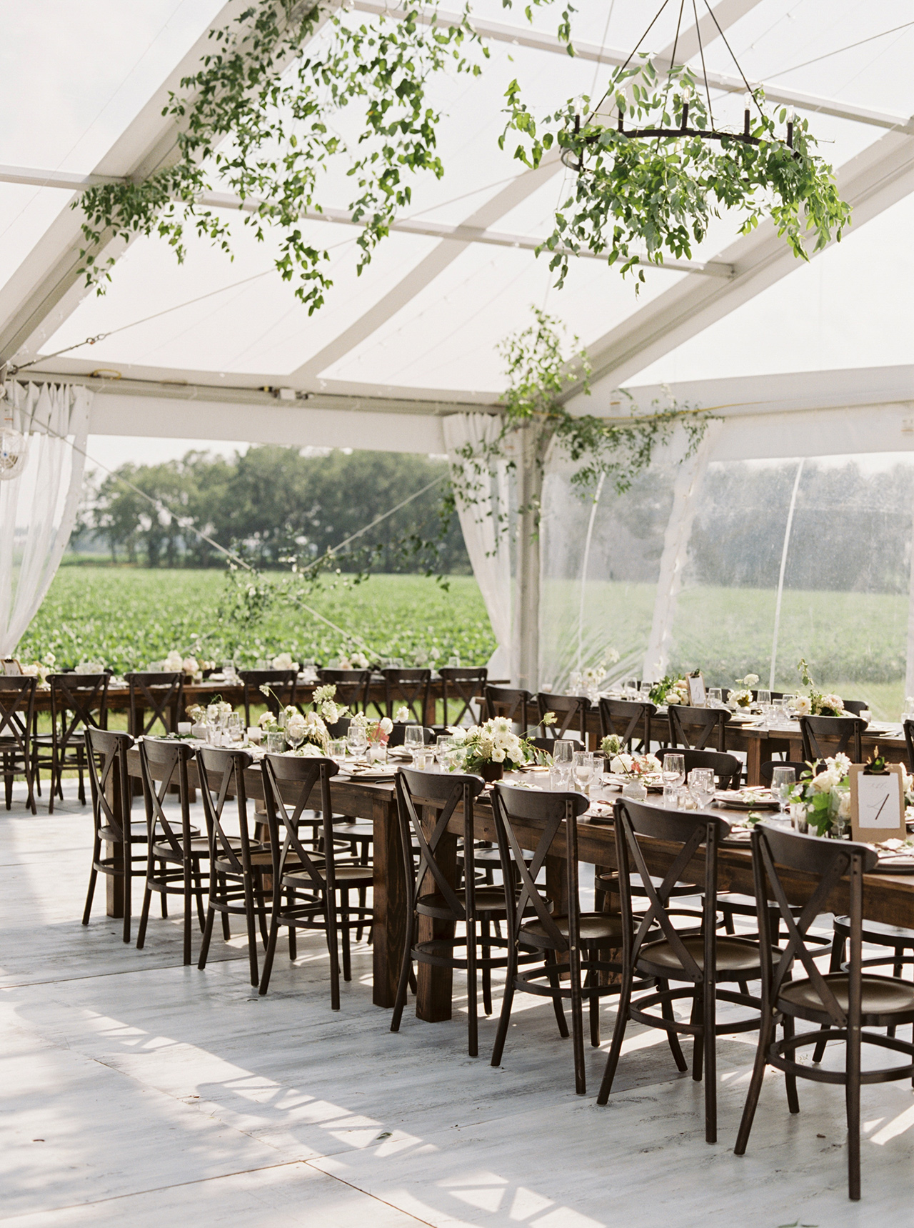 clear tent reception area draped greenery garlands