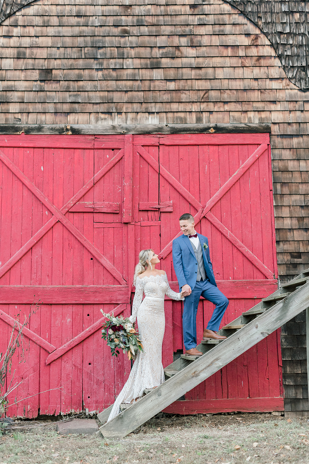 bride and groom on stairs next to red barn door