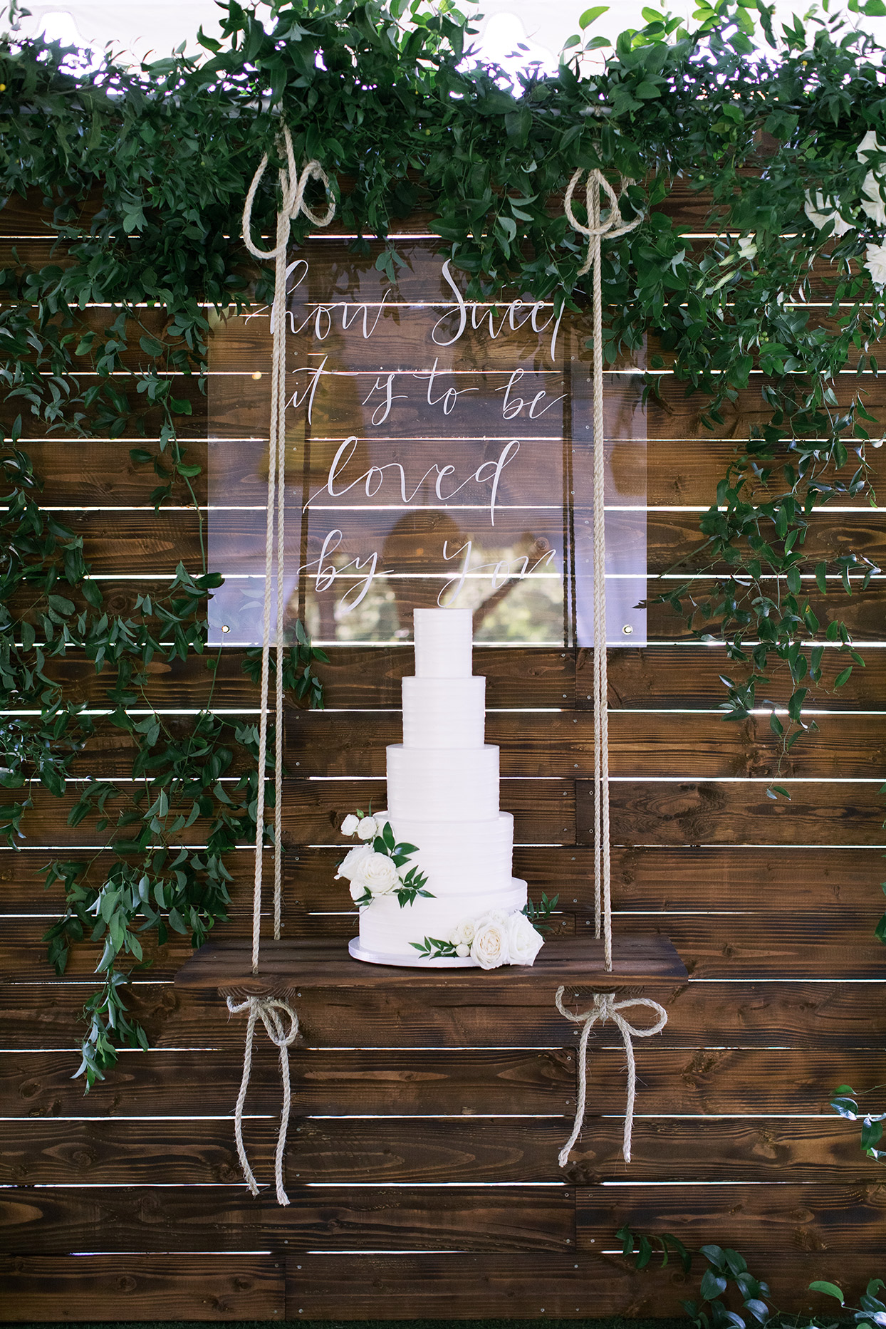 amanda will wedding cake suspended against wooden wall