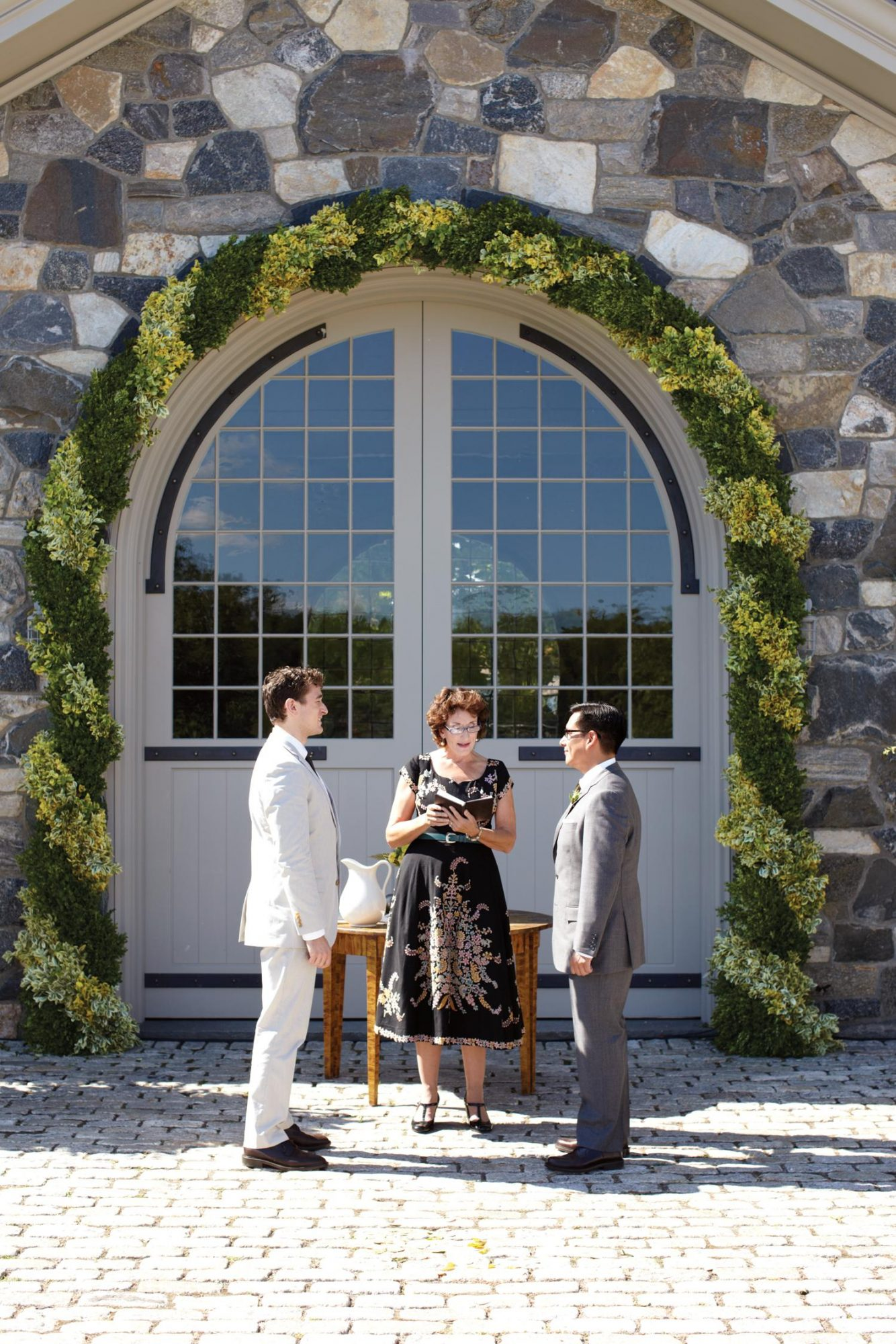 Couple getting married under arched backdrop