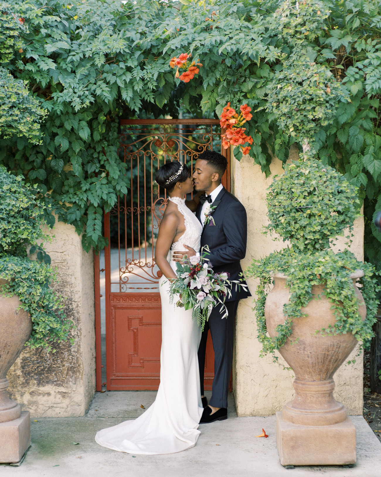 Chaya and Braxton in front of rustic garden door