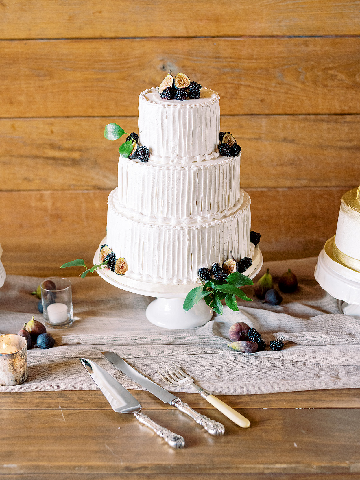 Claire and Dan's white three-tiered wedding cake with berries and figs