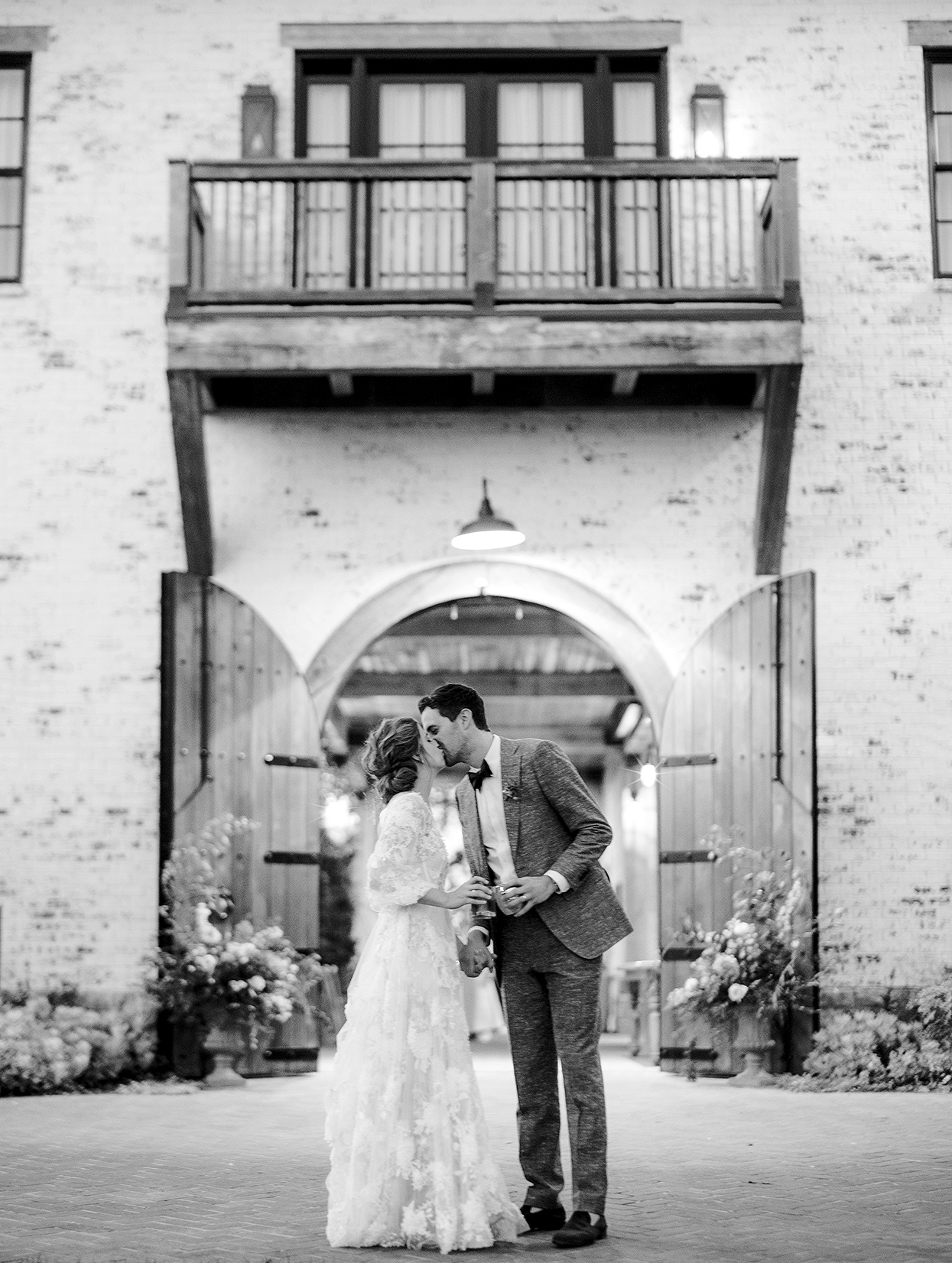 Claire and Dan kissing outside venue with glasses clinking