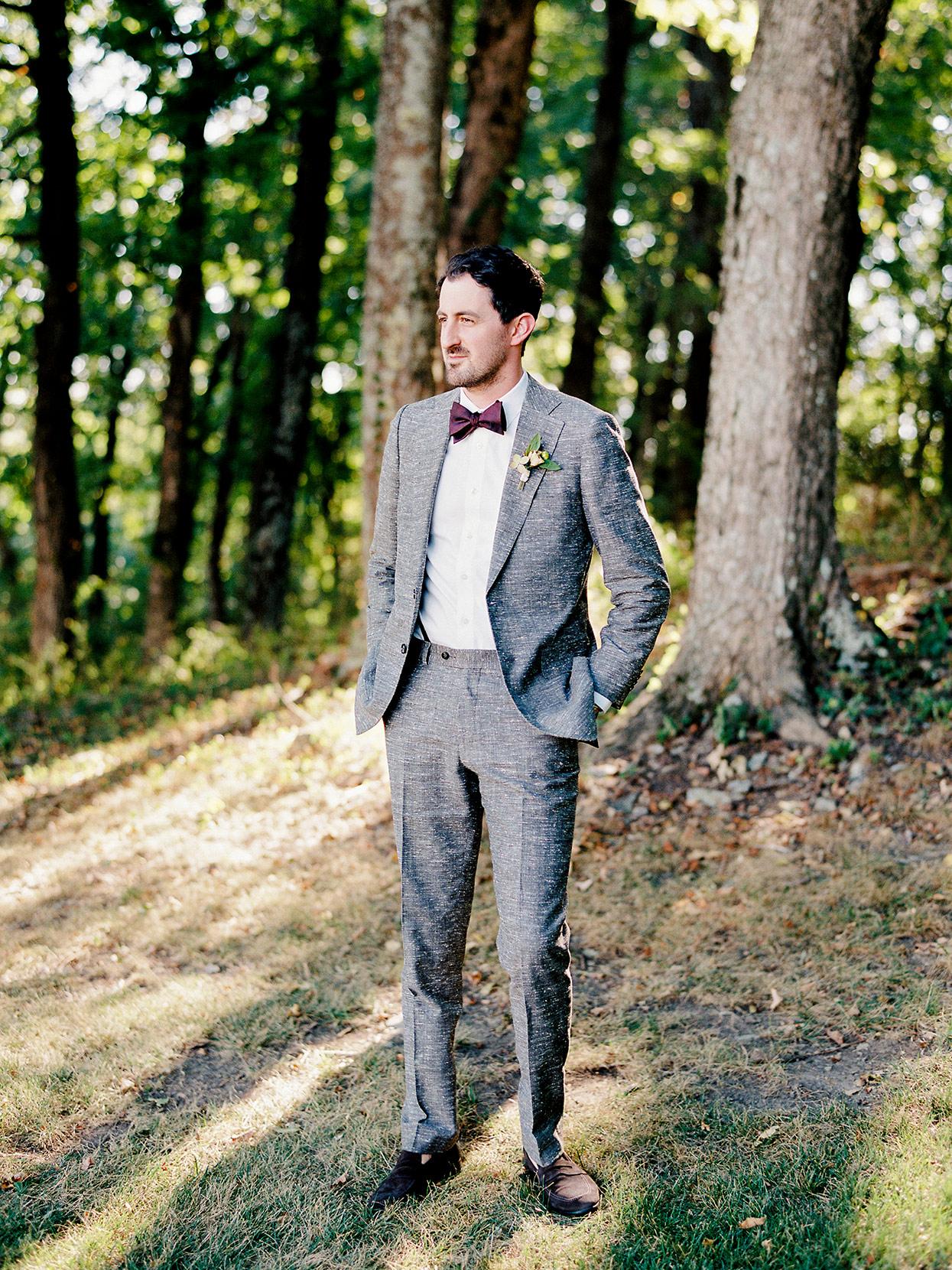 Portrait of groom Dan outside in gray suit near trees
