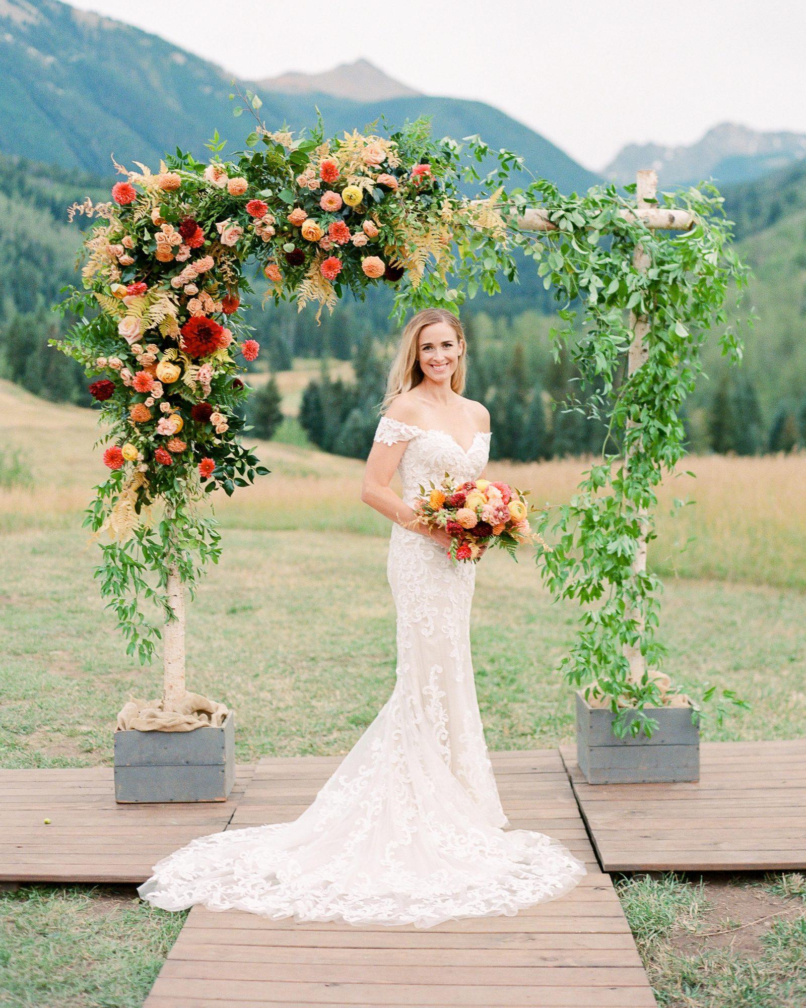 jill phil wedding bride solo portrait under floral ceremony arch